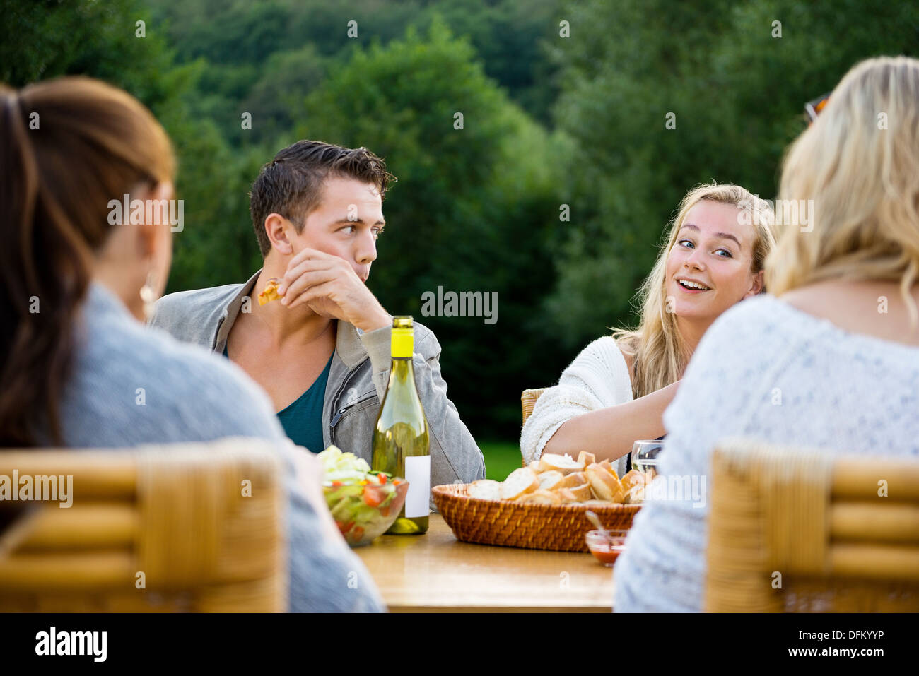 Young friends enjoying meal at garden party - Stock Image