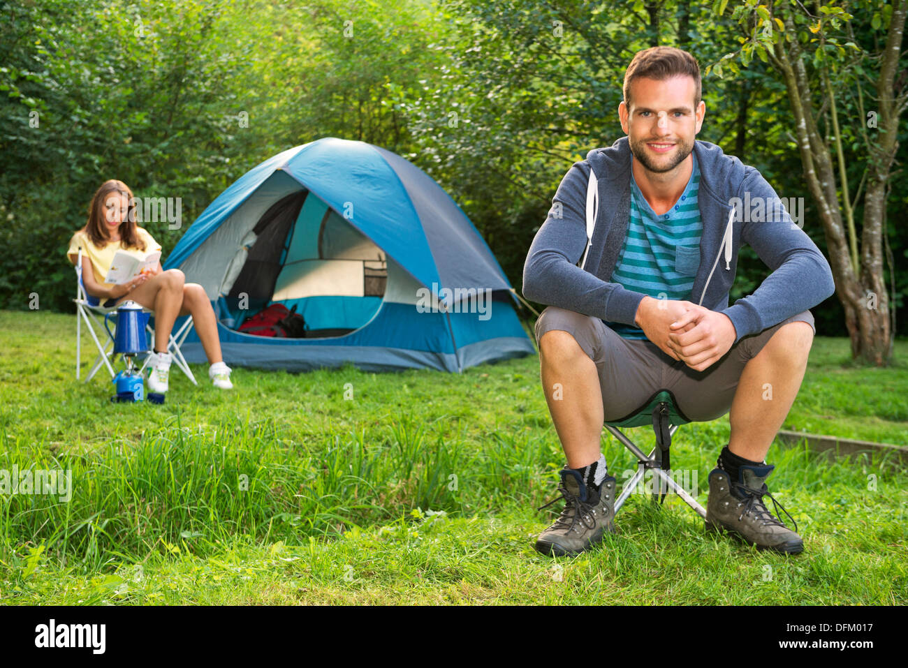 A young couple relaxing in front of a tent - Stock Image