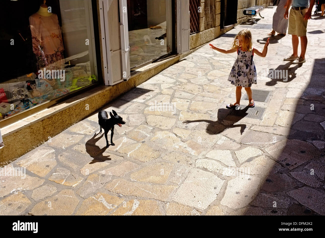 Girl watching dog in street, Palma, Mallorca - Stock Image