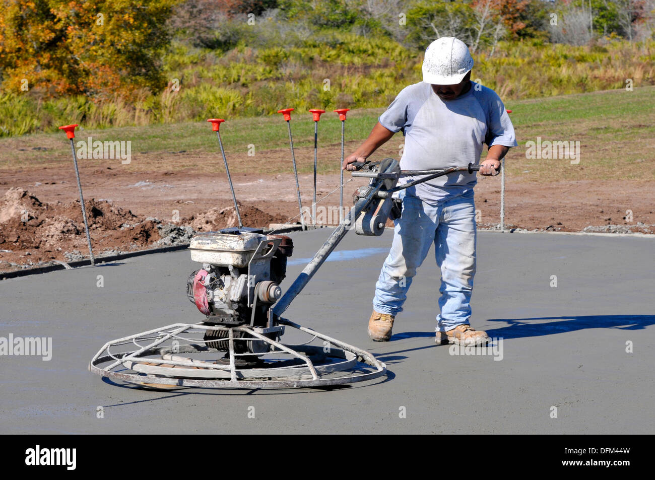 Latino hispanic Mason workers work to finish cement floor on new home construction Tampa Florida - Stock Image