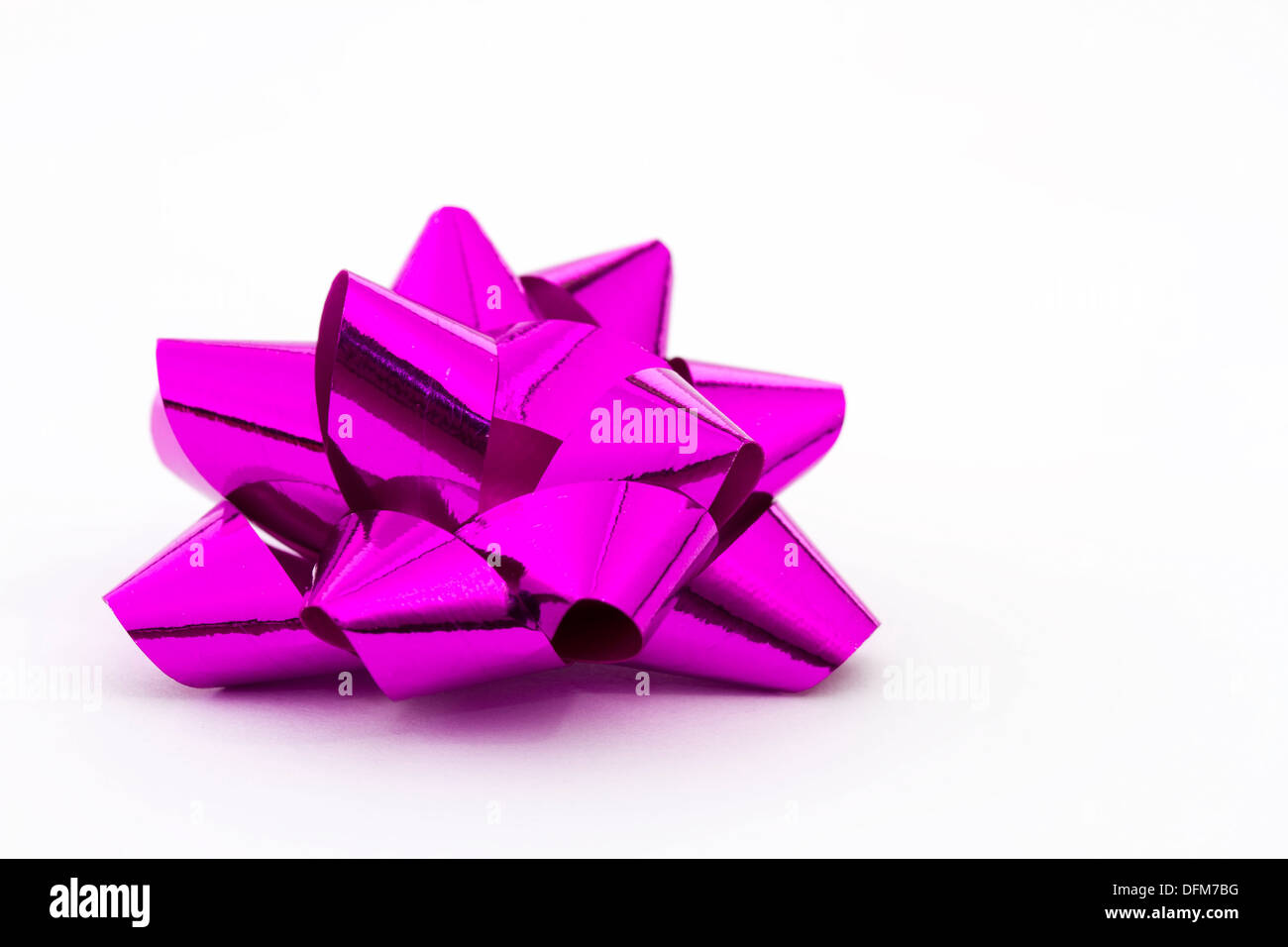 Pink christmas foil bow on white - Stock Image