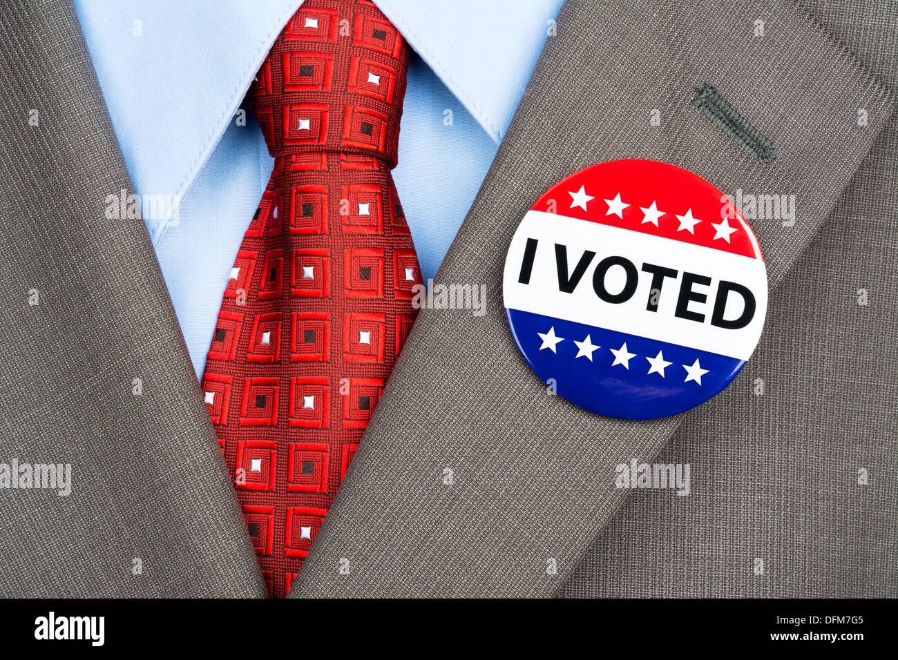 A businessman in a tan suit wearing his vote pin on his jacket lapel - Stock Image