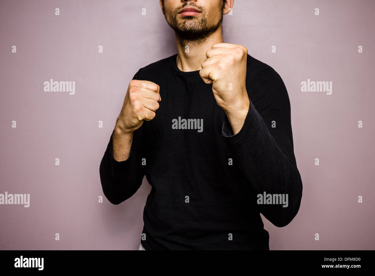 Young man raising his fists in preparation to fight - Stock Image