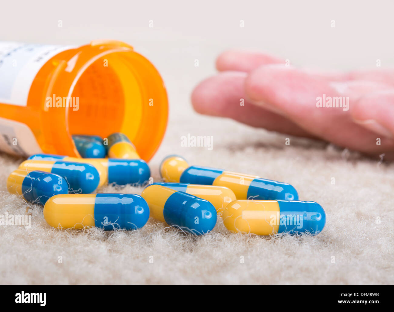 A person overdoses on prescription medication and lies unconscious on the floor - Stock Image