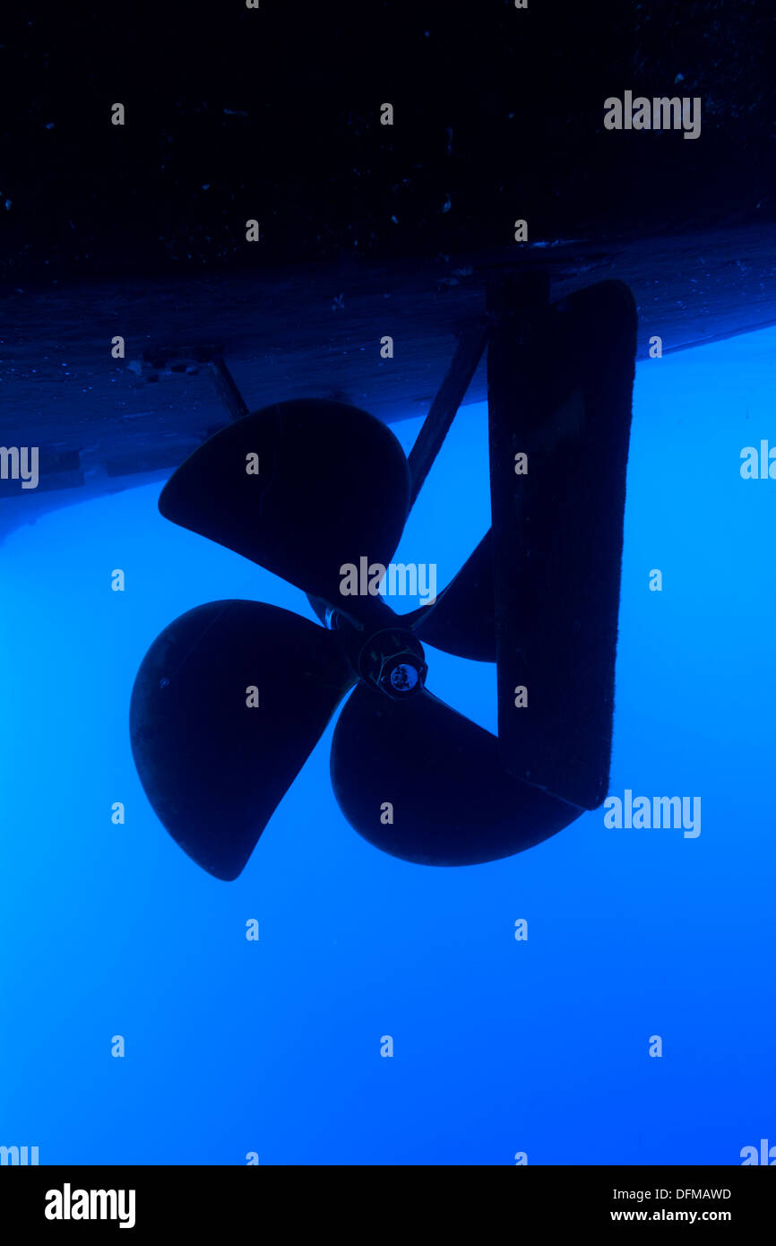 A boat propeller and rudder on a large vessel in blue water. - Stock Image