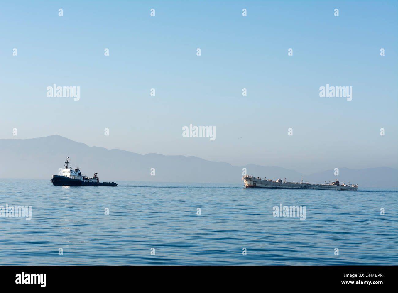 A tugboat towing a disabled freighter during an early morning, hazy day. - Stock Image