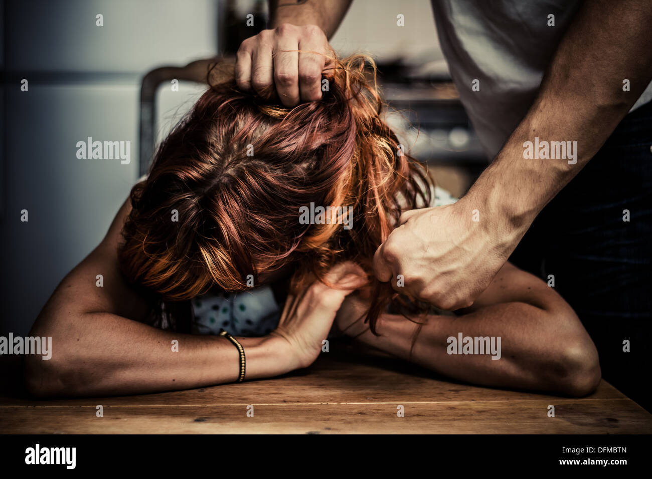 Man pulling the hair of his wife and threatening to punch her - Stock Image
