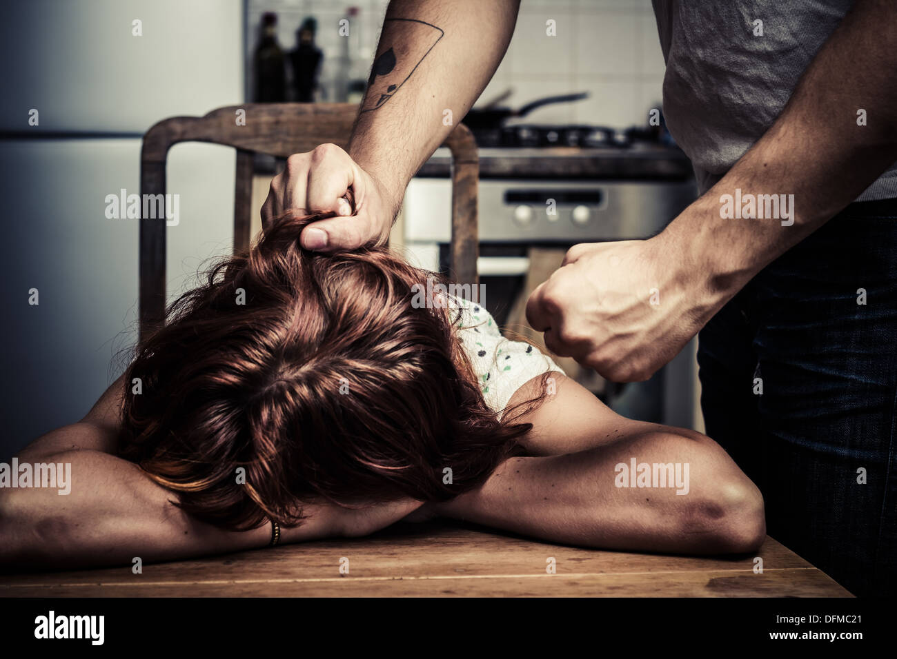 Man pulling his wife's hair in kitchen - Stock Image