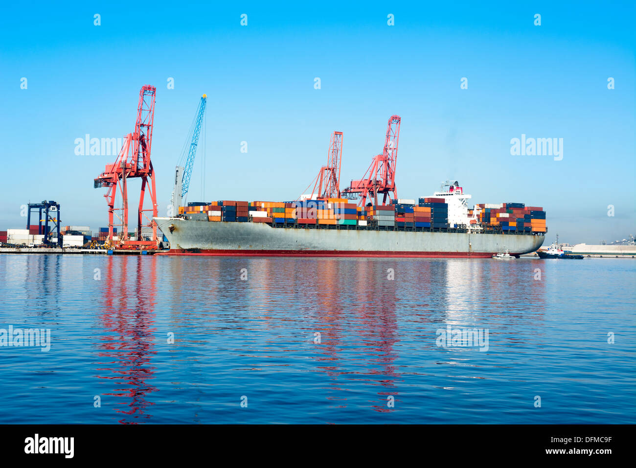 A cargo freighter with colorful cargo containers being loaded for international transportation - Stock Image