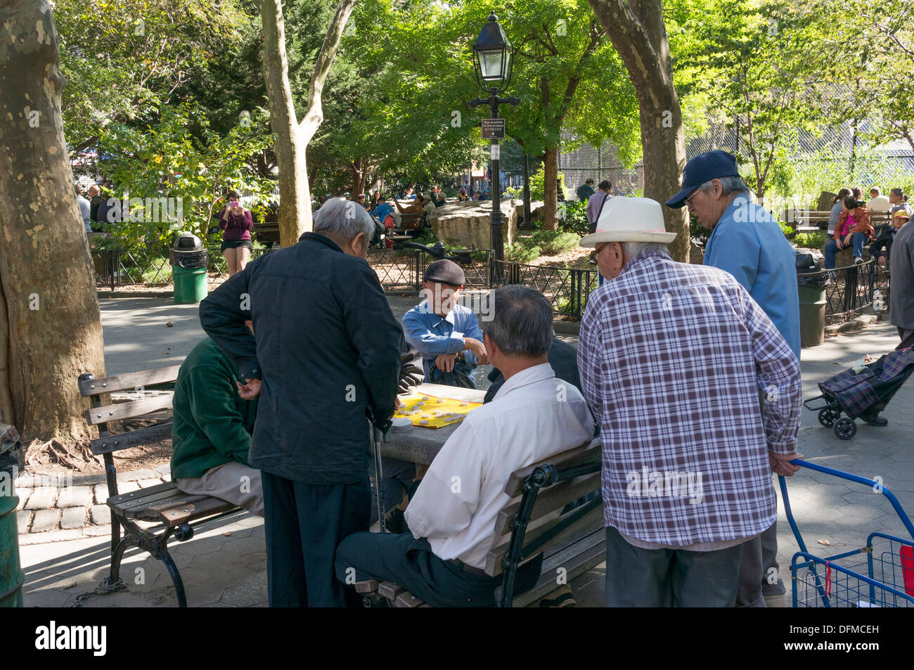 Senior Asian men playing Chinese Chess in Columbus Park in Chinatown in NYC (Xiangqi) Stock Photo