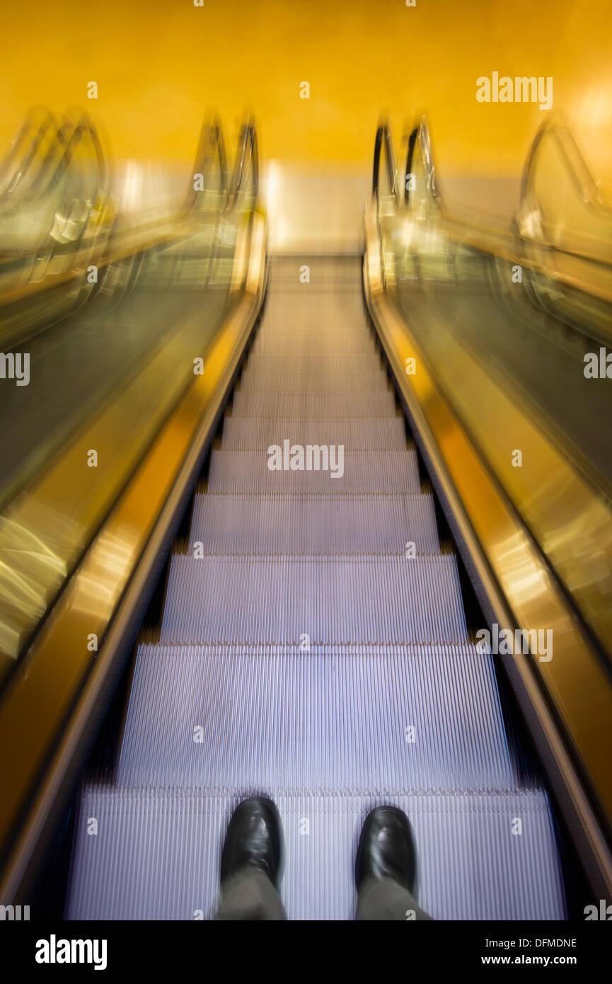 Businessman's Feet Going Down Escalator - Stock Image