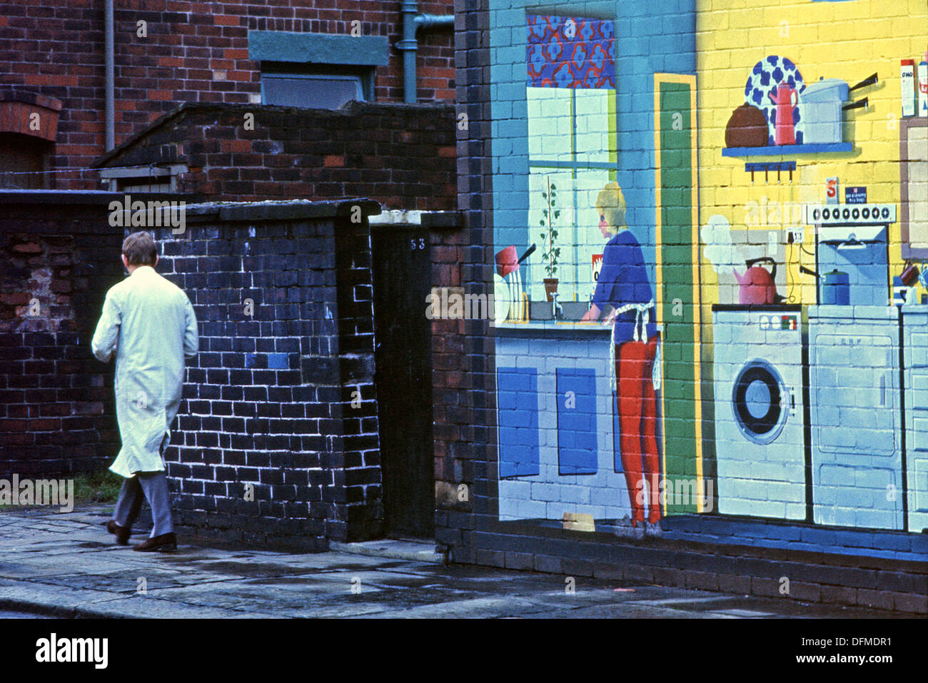 Man Walking Past Wall Mural INSIDE OUT HOUSE On The Gable End Of A Rochdale  House Lancashire UK 1975 KATHY DEWITT