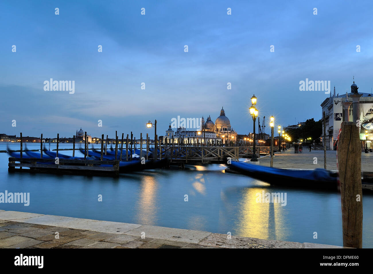 Beautiful image captured during the blue hour in Venice, foreground we see the typical Venetian Gondolas moored at the pier, to - Stock Image
