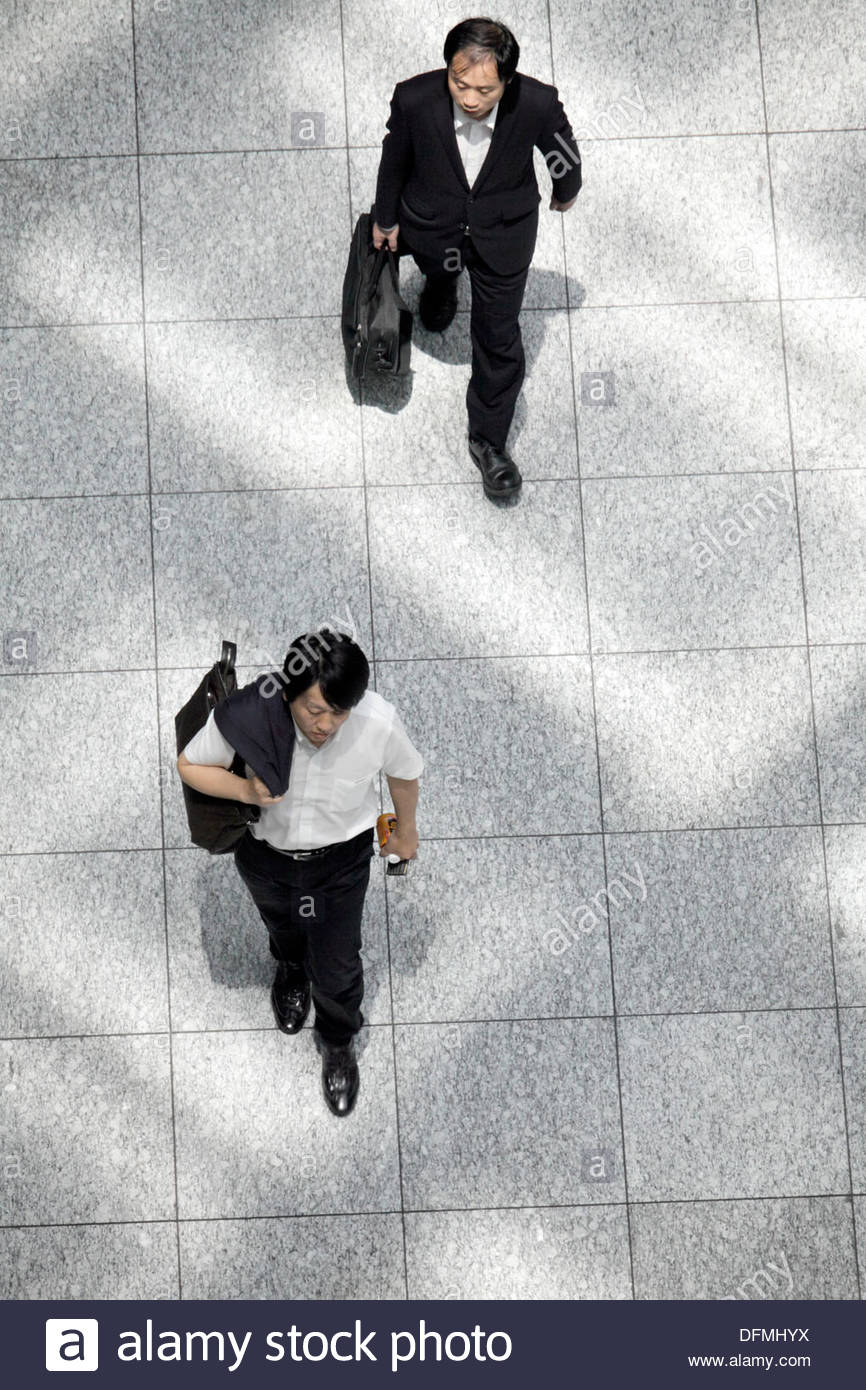 overhead view of business people walking with light from roof pattern on the floor Stock Photo