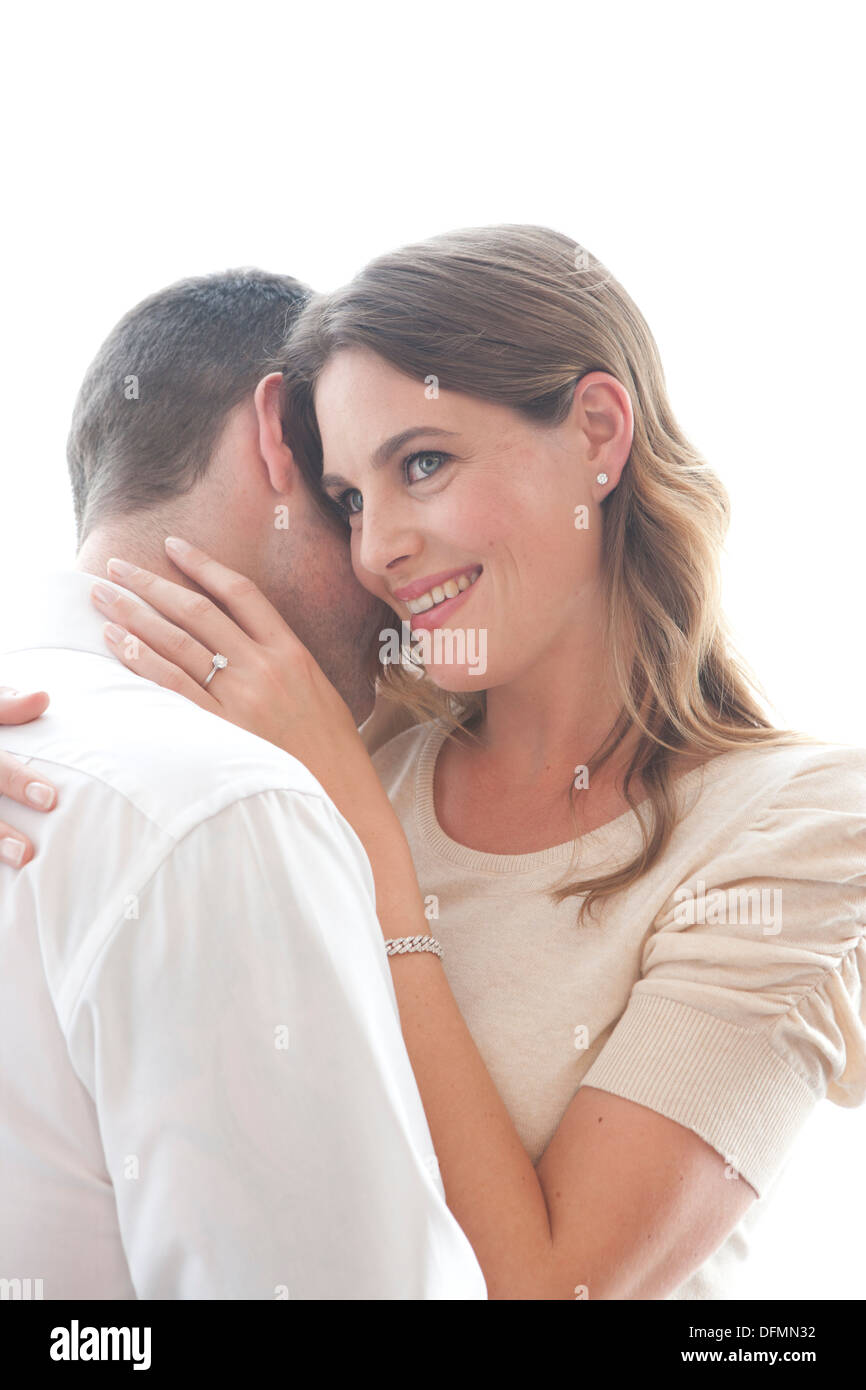 High key image of a late 20s/early 30s male and female couple embracing and in love. Woman giving a knowing and thoughtful look. - Stock Image