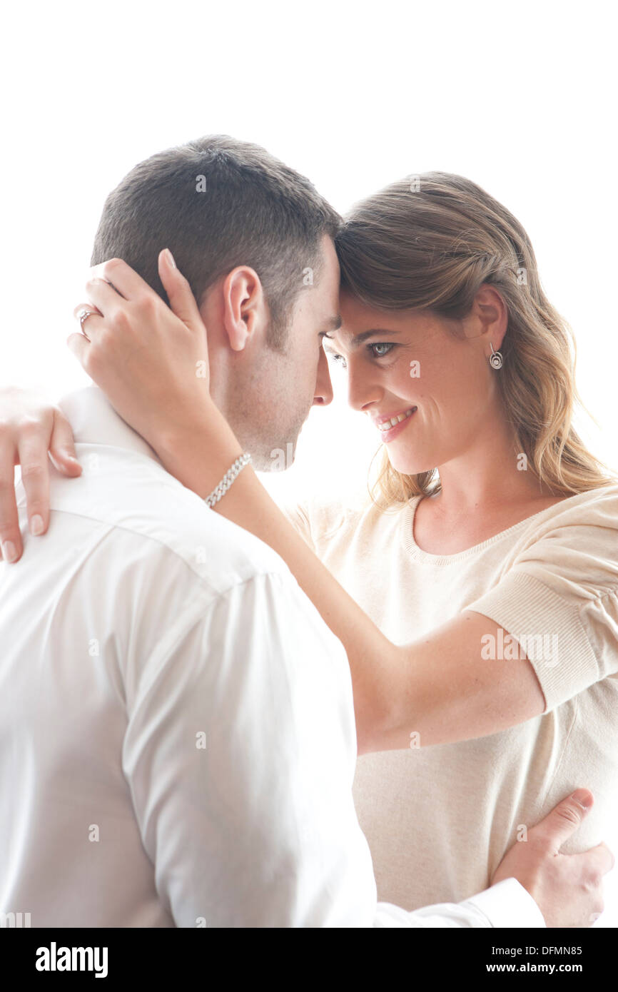 High key image of a late 20s/early 30s male and female couple embracing and in love - Stock Image