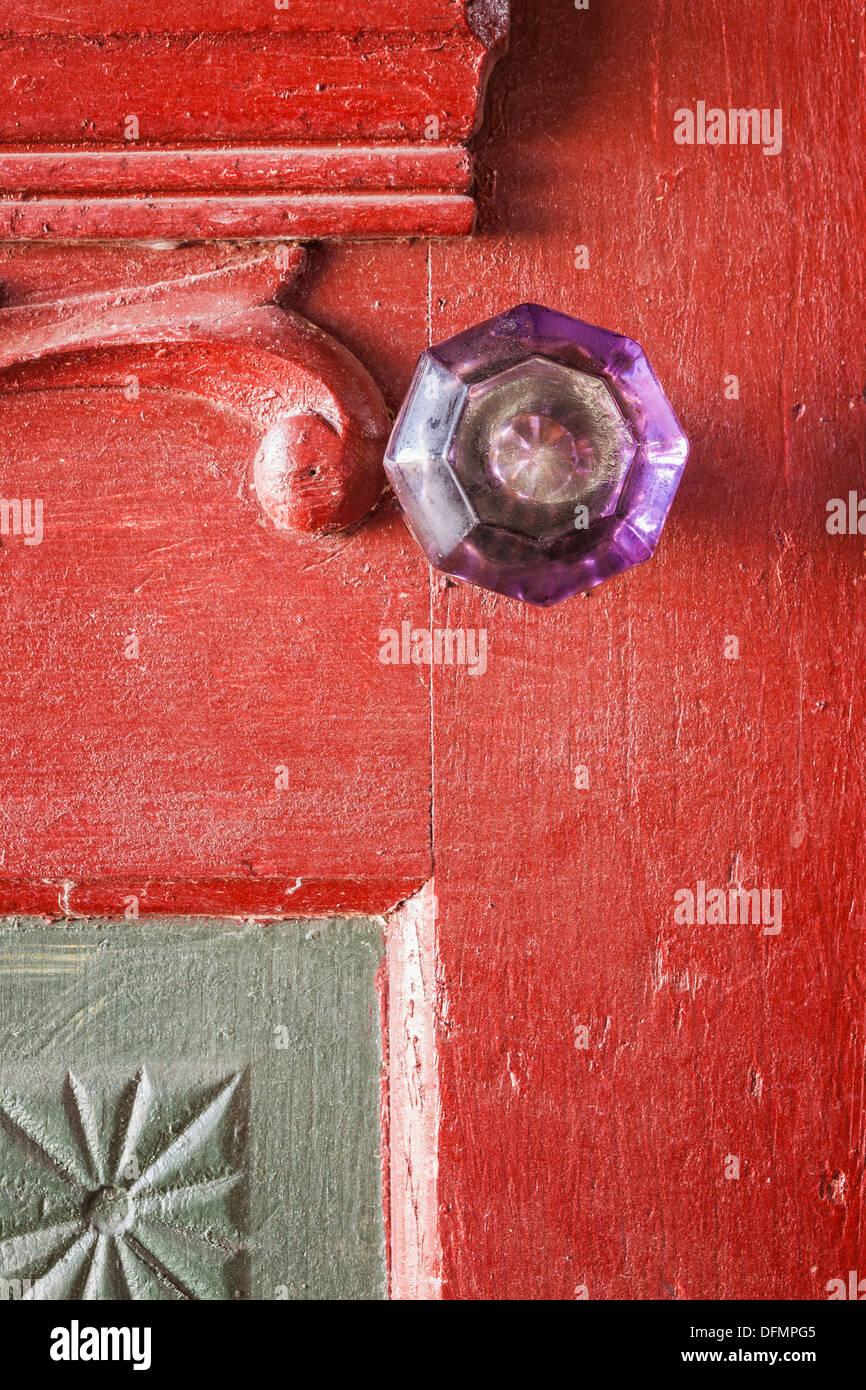 Purple antique crystal doorknob on red door - Stock Image
