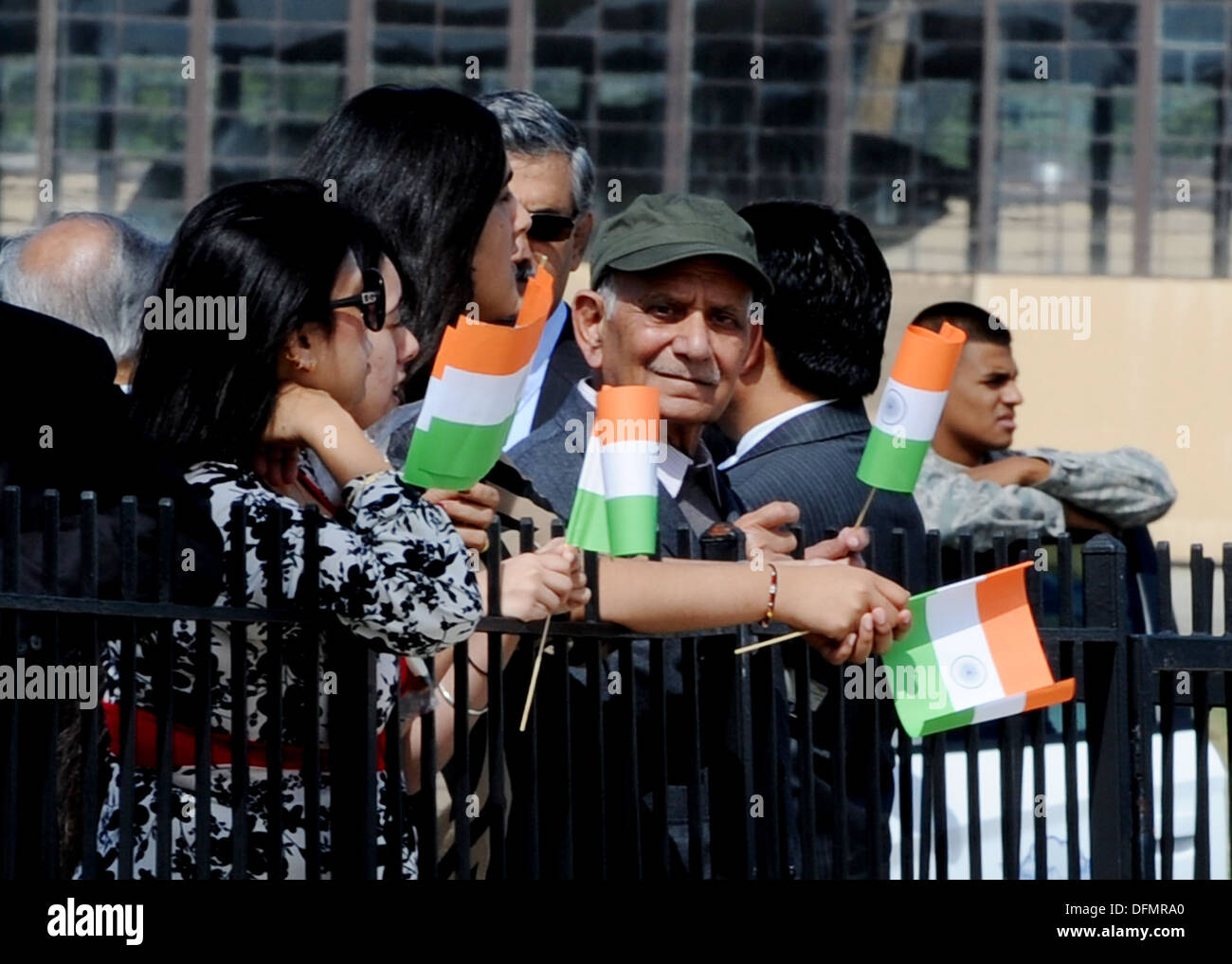 People line the fence and wave the flag of India to welcome Prime Minister of India Dr. Manmohan Singh as he arrives to Joint Base Andrews, Md., Sept. 26, 2013. The Prime Minister arrived for a two-day visit to meet with President Barack Obama and First L - Stock Image