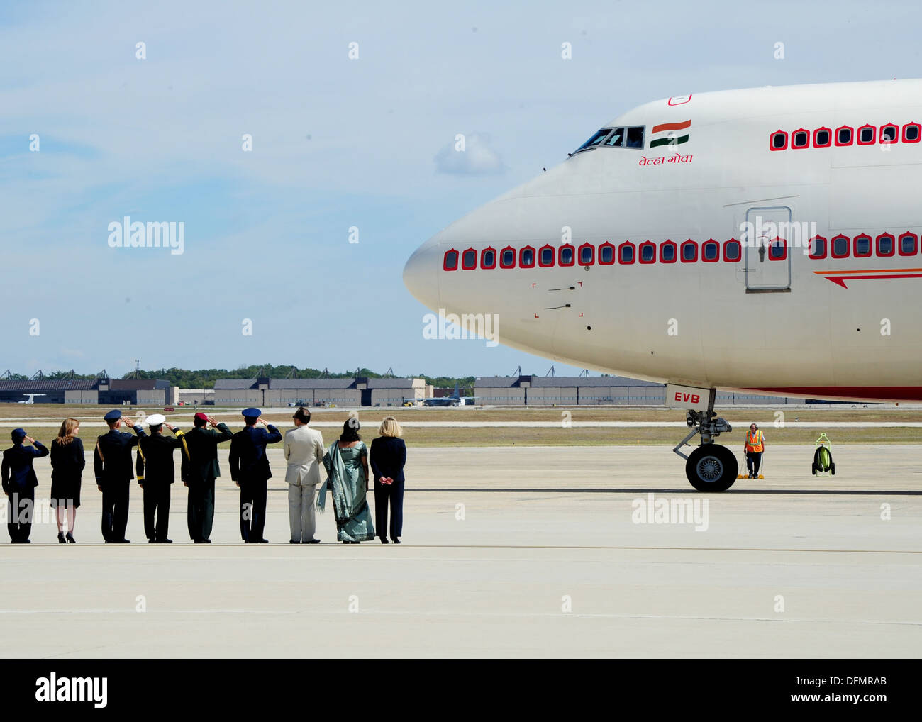 Military member's renders a salute as an aircraft carrying Prime Minister of India Dr. Manmohan Singh arrives at Joint Base Andrews, Md., Sept. 26, 2013. The Prime Minister arrived for a two-day visit to meet with President Barack Obama and First Lady Mic - Stock Image