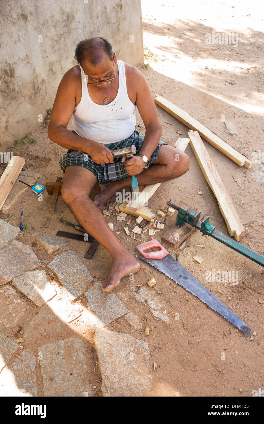 Indian man doing carpentry outside his home in a rural indian village. Andhra Pradesh, India - Stock Image