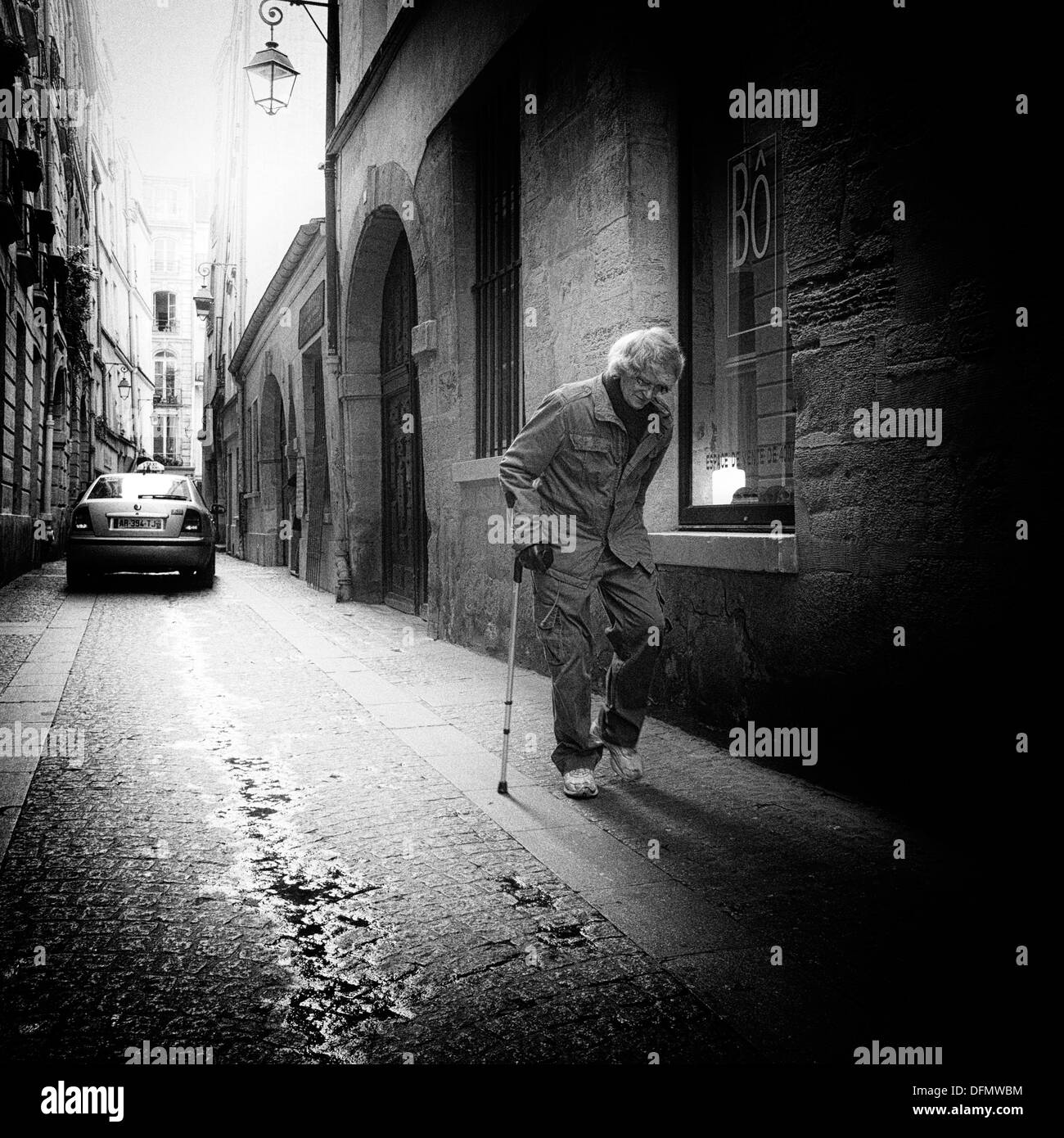 Lame man walking in the 10th arrondissement of Paris, photographed with pinhole camera - Stock Image