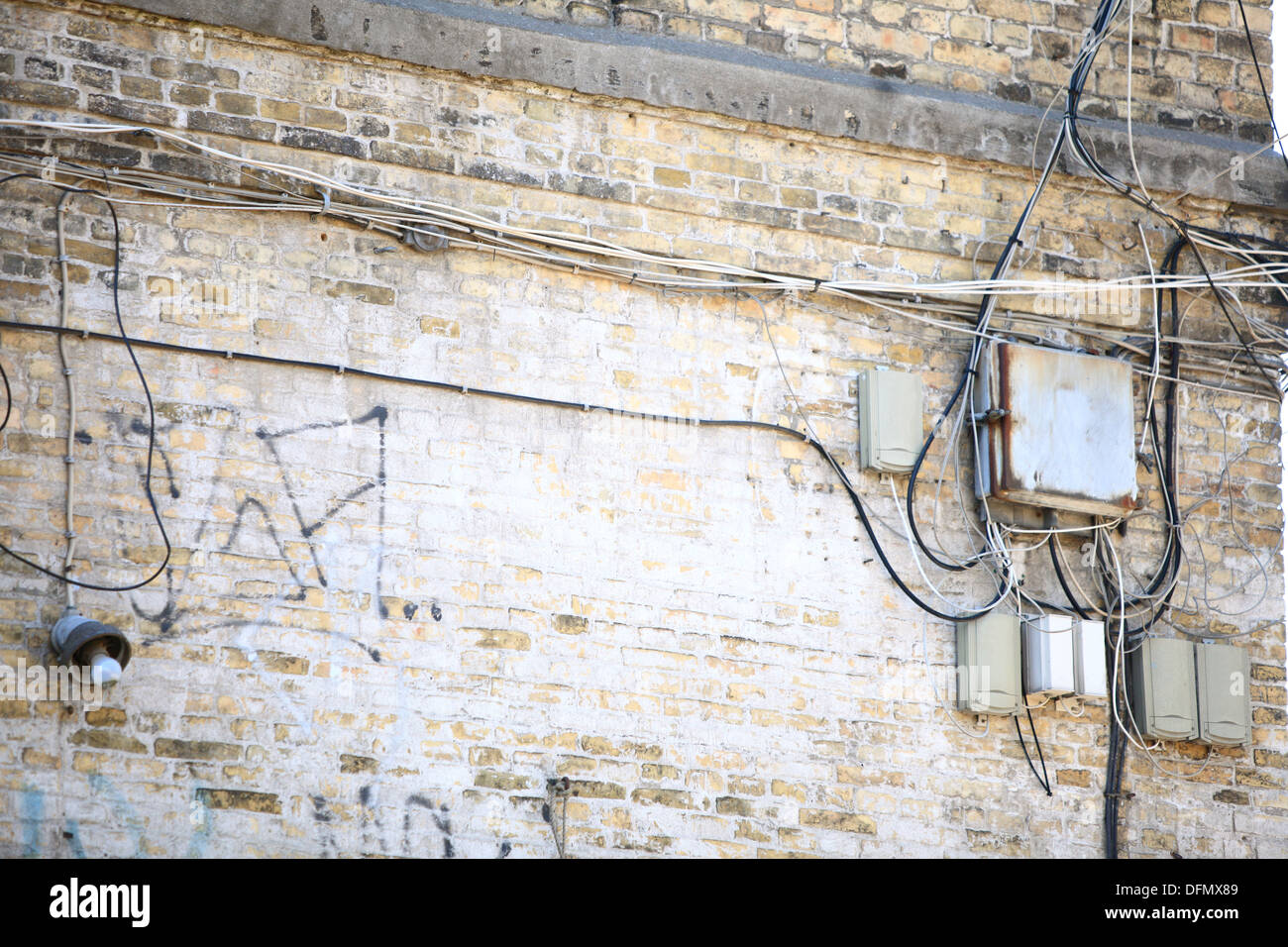 Electric controller box and tangle of cables wires on the brick wall Stock Photo