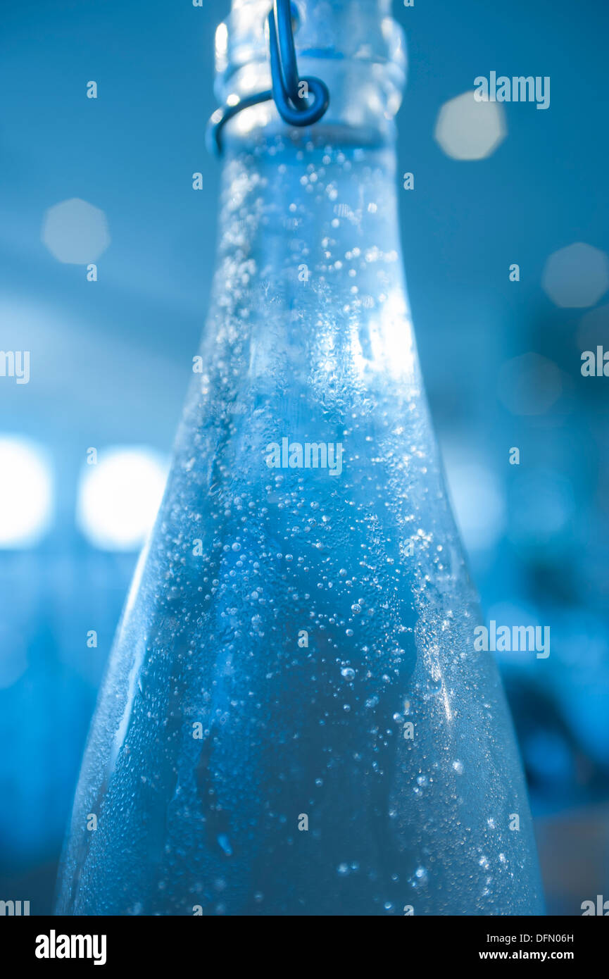 Water condensing on a bottle of cold water in a restaurant. - Stock Image