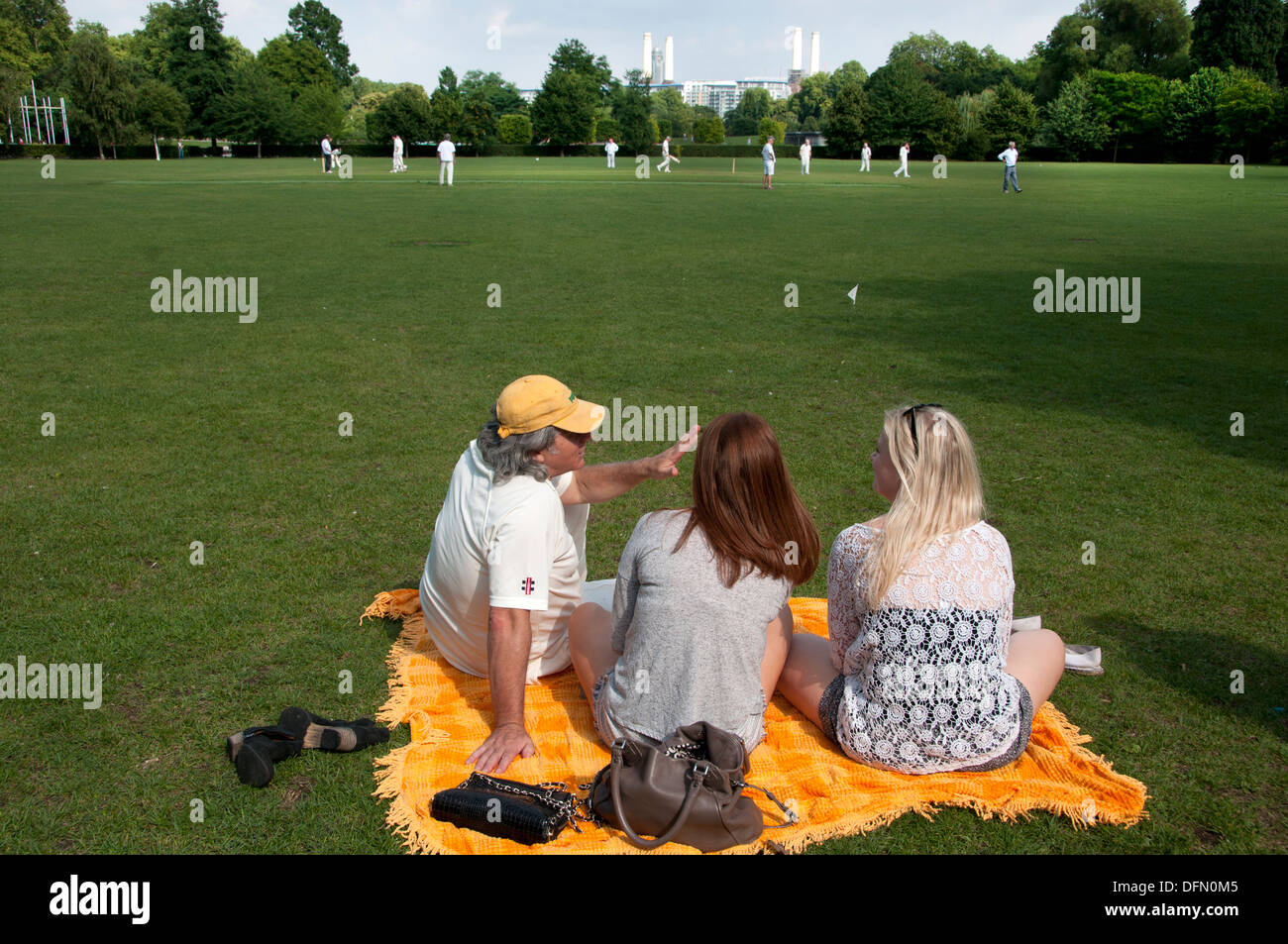 Battersea, London 2013. Amateur cricket match.A small group watch the game with power station in background - Stock Image