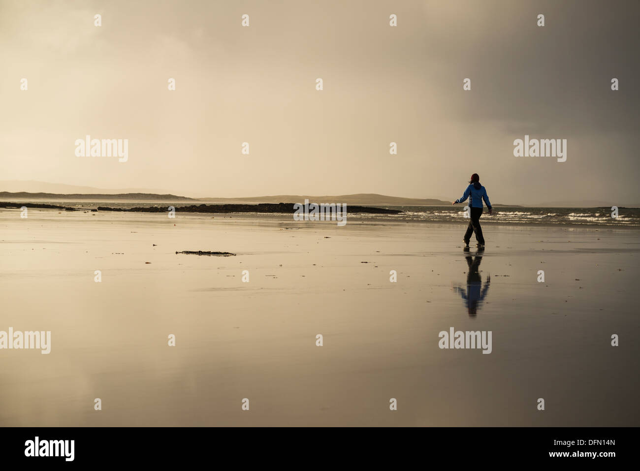 Reflection of woman walking on Traigh Lingeigh beach, North Uist, Outer Hebrides, Scotland - Stock Image