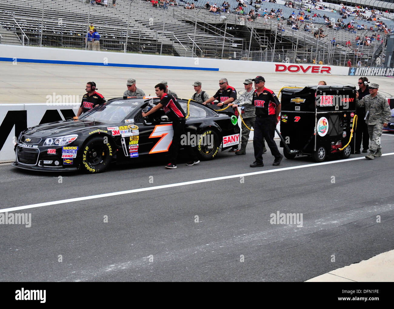 Members of Dave Blaney's pit crew and honorary pit crew members from Dover Air Force Base push Blaney's No. 7 Tommy Baldwin Racing Chevy down pit road before qualifying for the AAA 400 Sept. 27, 2013, at Dover International Speedway, Dover, Del. The honor - Stock Image