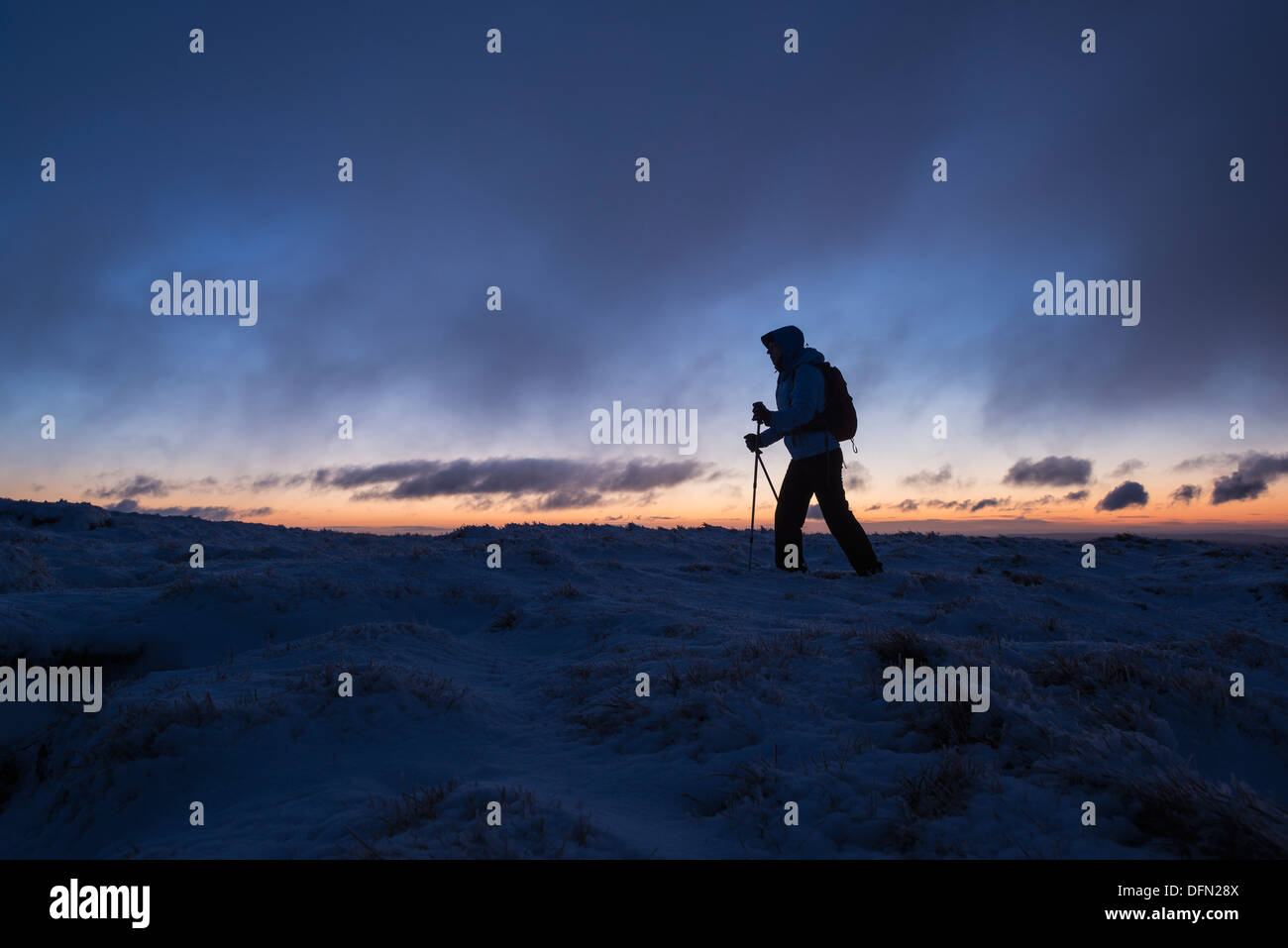 Silhouette of hiker on wintry summit of Corn Du at dawn, Brecon Beacons national park, Wales - Stock Image