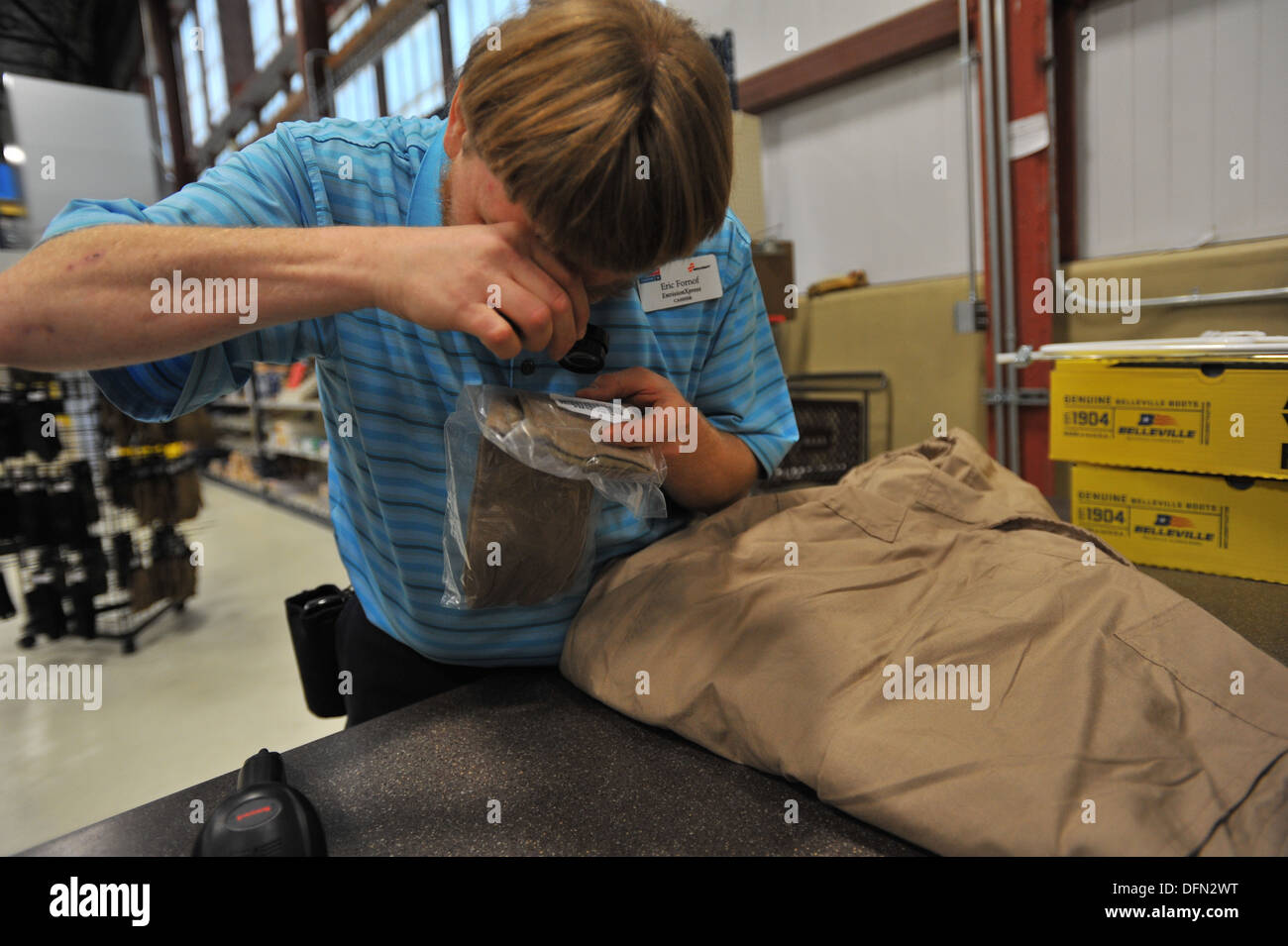 Eric Fornoff, Envision cashier, looks through his pocket magnifier to read a price tag at the base supply store at Fairchild Air Force Base, Wash., Sept. 30, 2013. Fornoff is legally blind and has been working on Fairchild for eight years. - Stock Image