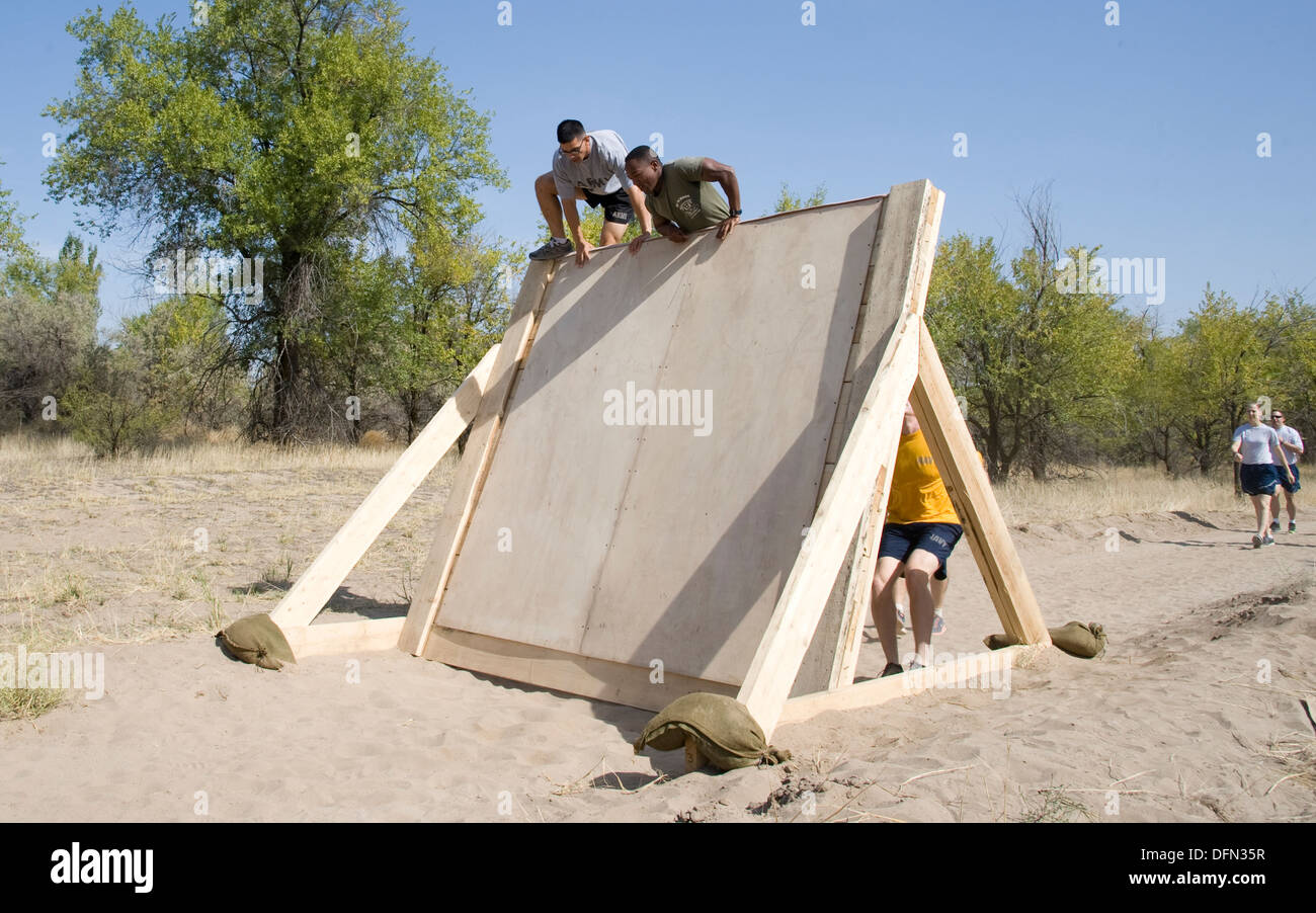 """Service members climb the first obstacle in the """"Filthy 5K"""" at Transit Center at Manas, Kyrgyzstan, Sept. 29, 2013. Stock Photo"""
