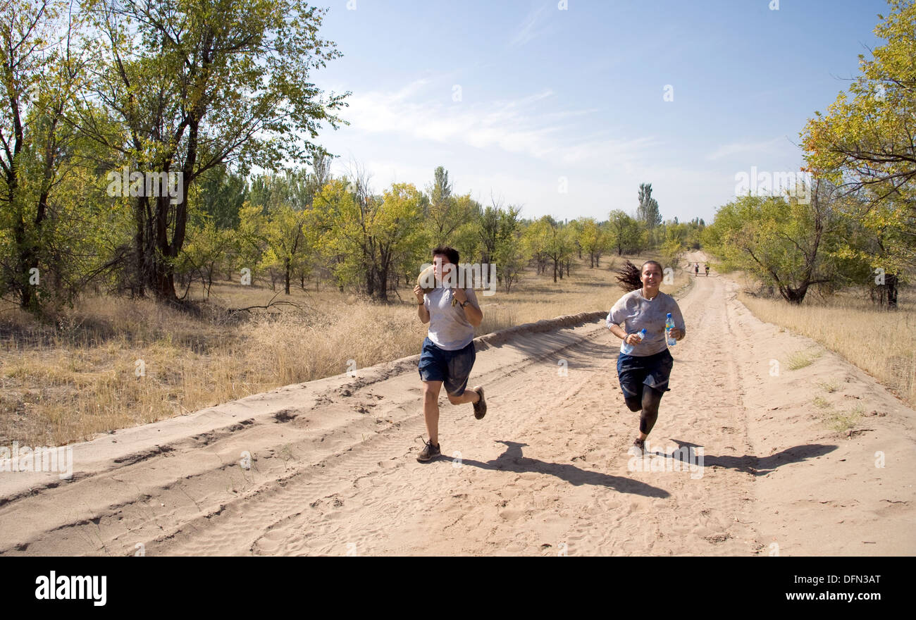 """Tech. Sgt. Wendy Corbett, 376th Expeditionary Security Forces Squadron, Transit Center Access Point 2nd in charge, left, and her teammate Staff Sgt. Patricia Eckles, 376 ESFS, military working dog handler, right, race to the finish during the """"Filthy 5K"""" - Stock Image"""