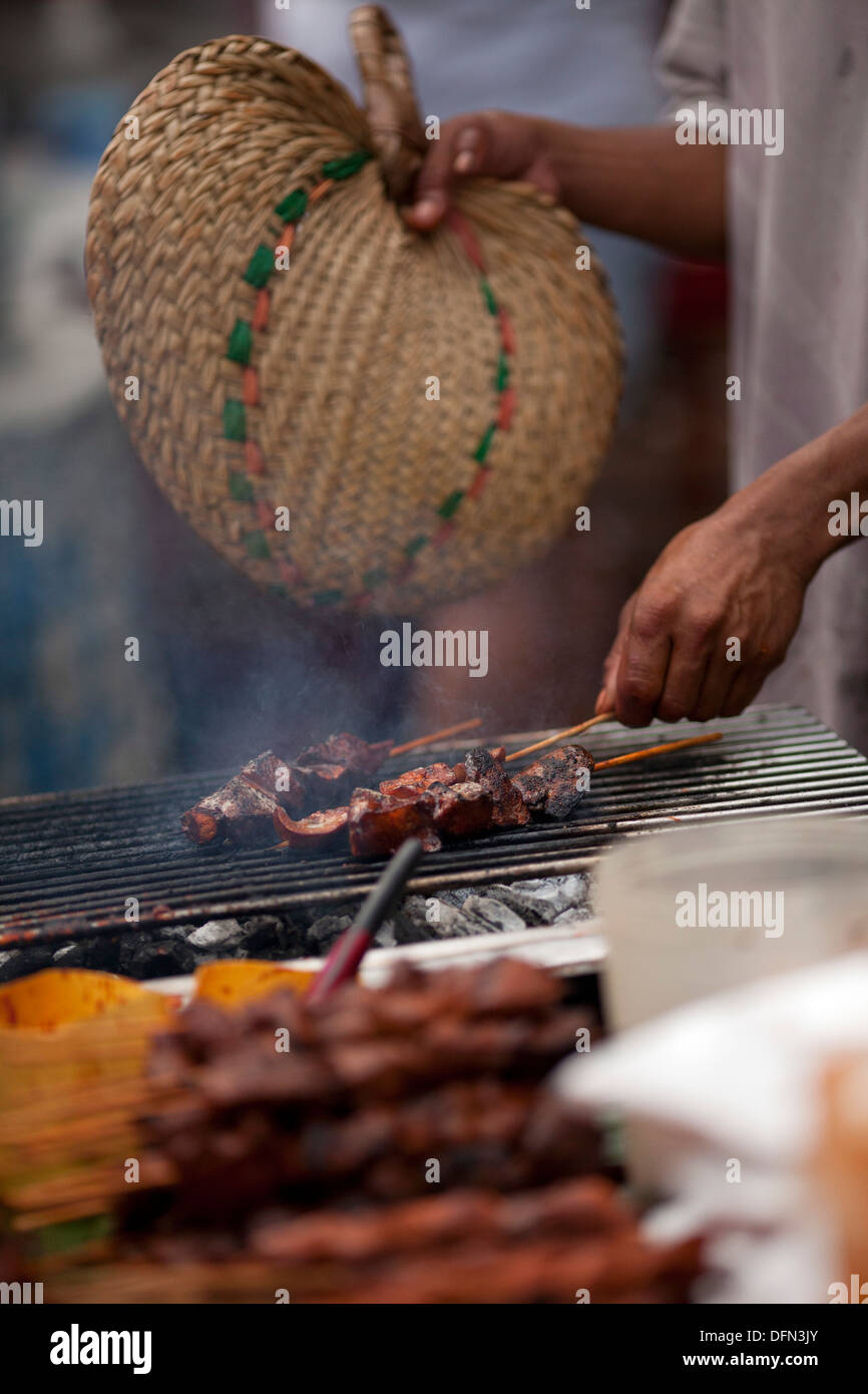 A street vendor cooks skewered chicken parts on a charcoal grill in Baclaran, Manila, Philippines. Stock Photo