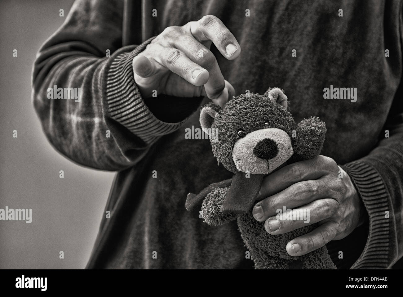 Man whacking teddy bear, child abuse concept - Stock Image