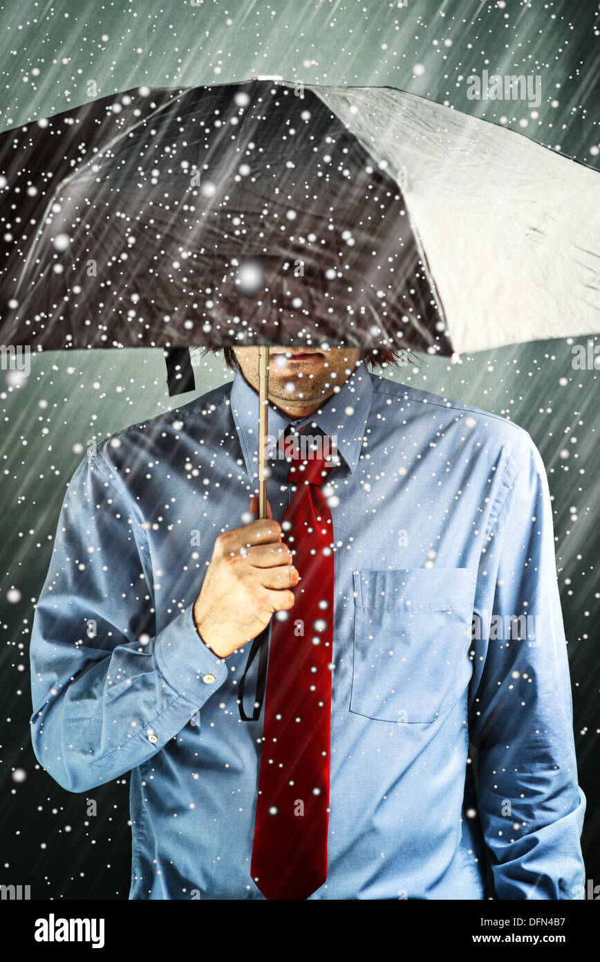 Businessman with black umbrella protecting himself from the storm. Financial problem, economic crisis, hard times concept. - Stock Image