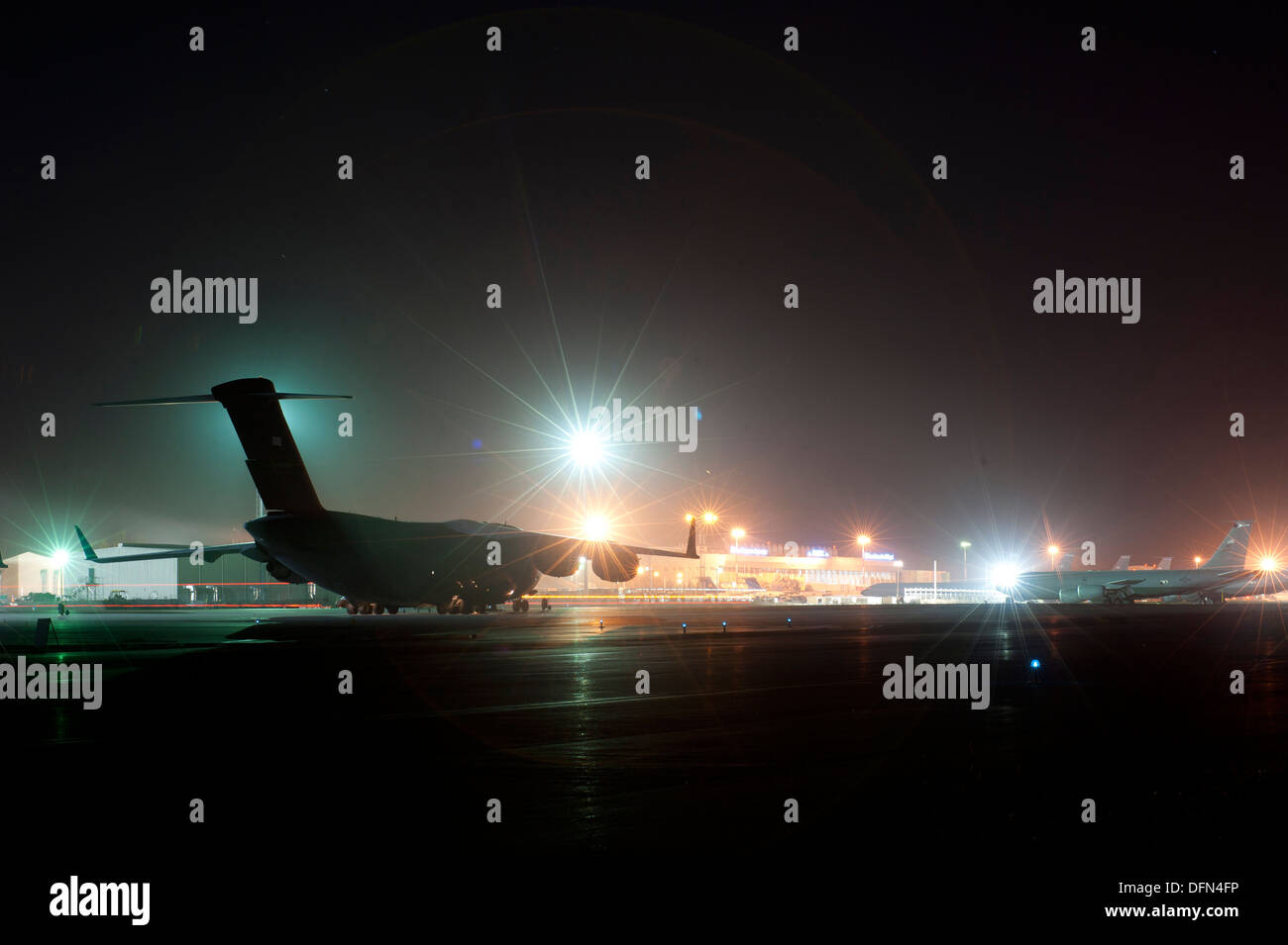 Bright lights illuminate the flightline and maintainence work stations for night operations at Transit Center at Manas, Kyrgyzstan, Oct. 2, 2013. The flight line is shared with the Kyrgyz Manas International Airport. - Stock Image