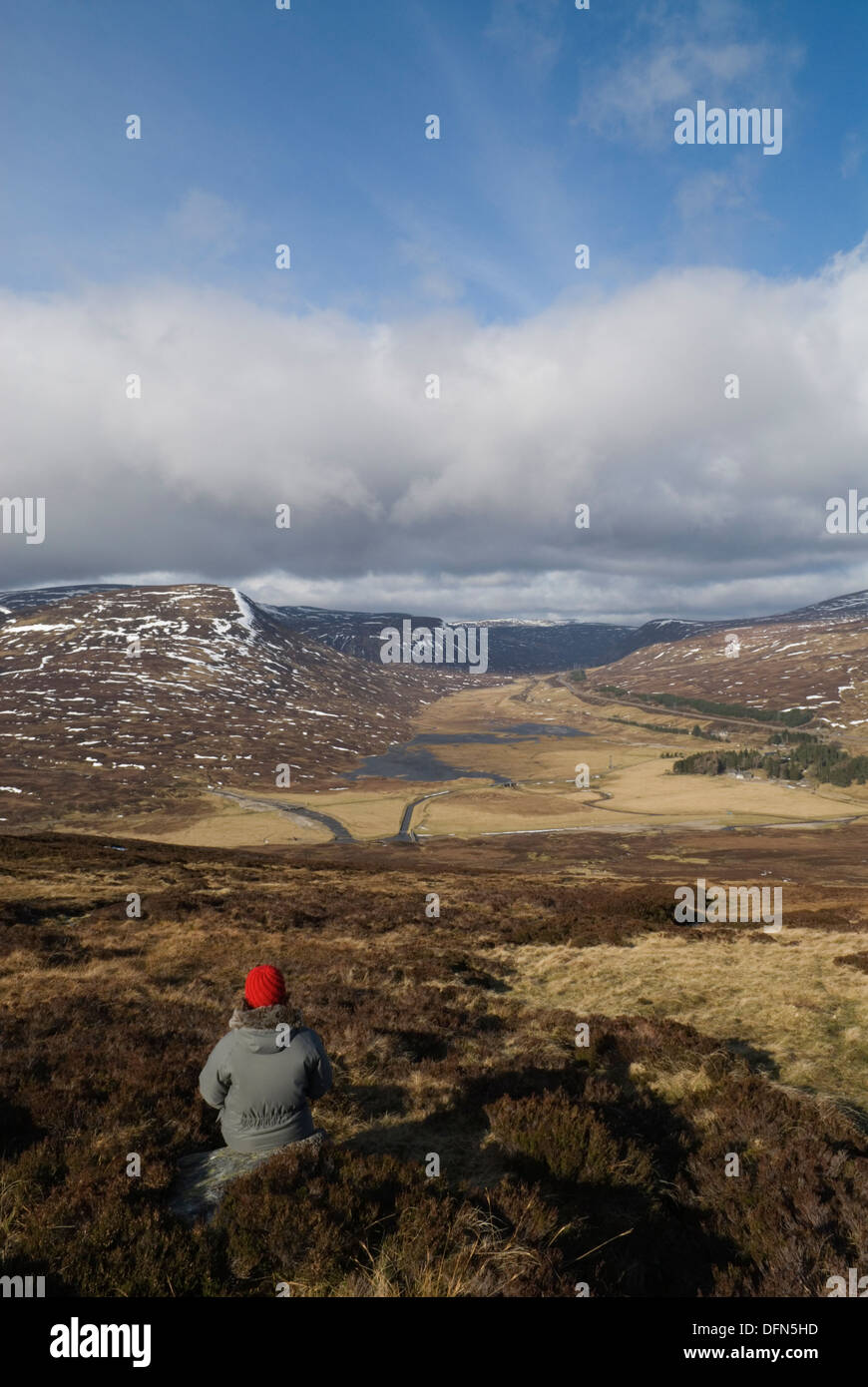 Female hillwalker admiring the view up the Pass of Drumochter from the slopes of the corbett Meall na Leitreach. - Stock Image