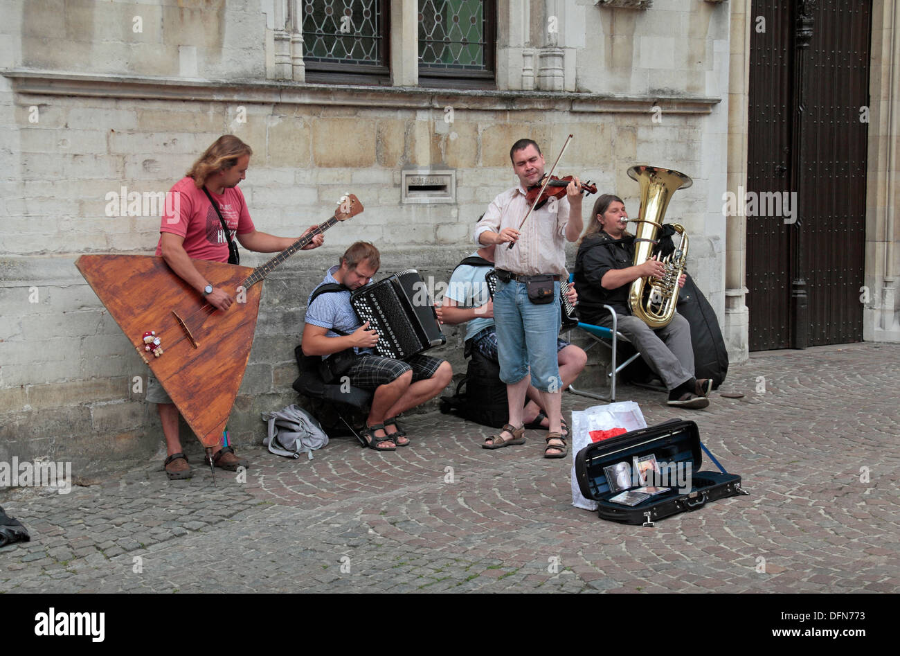 Street musicians, including the amazing looking balalaika, in historic Bruges (Brugge), West Flanders, Belgium. - Stock Image