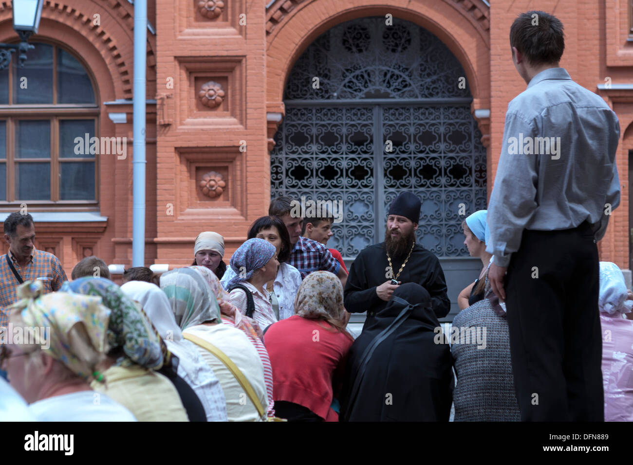 Russian Orthodox priest with congregants by Resurrection Gate Church - Stock Image