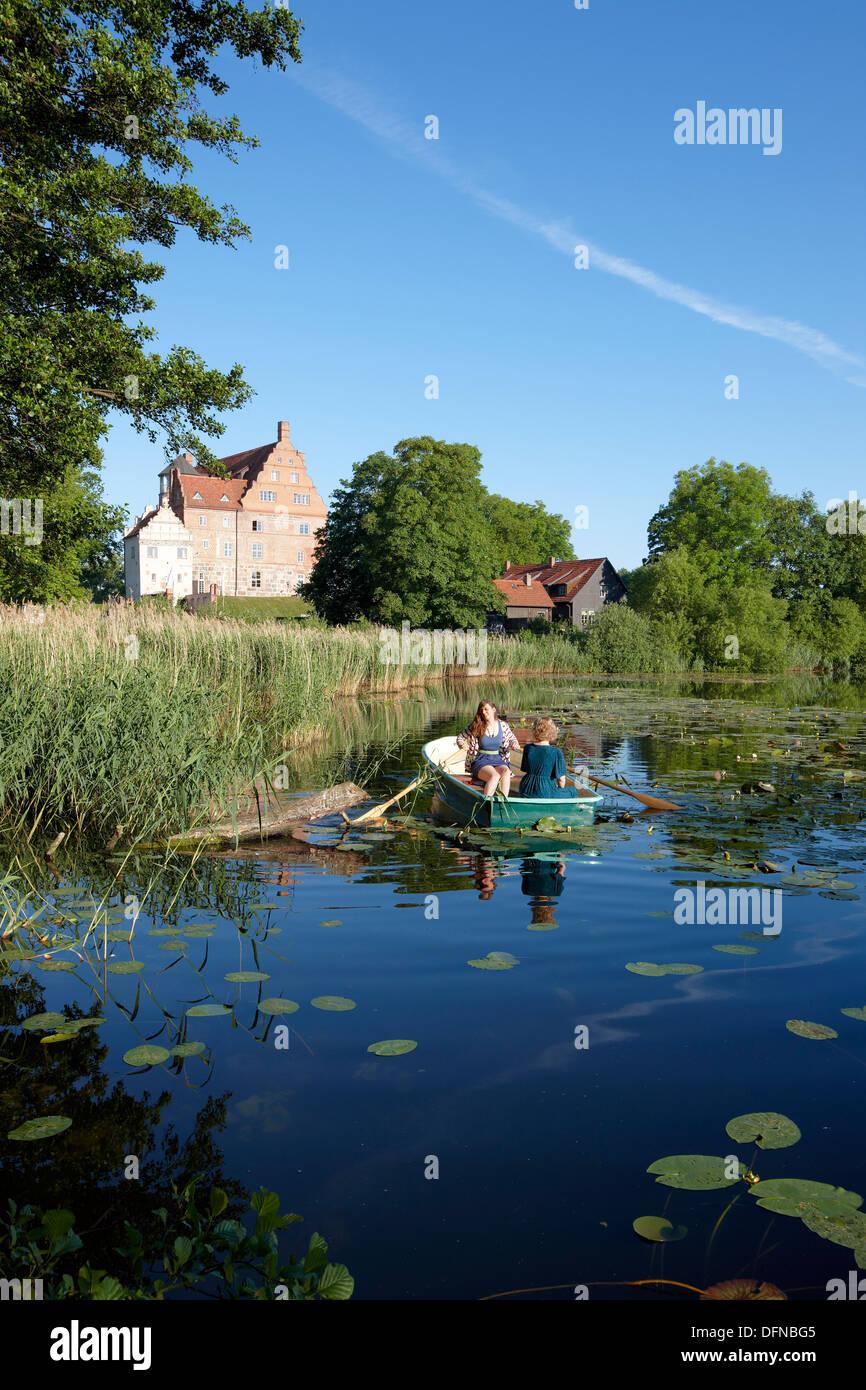 Two women in a rowing boat on lake Ulrichshusen, Ulrichshusen castle, Mecklenburg-West Pomerania, Germany - Stock Image