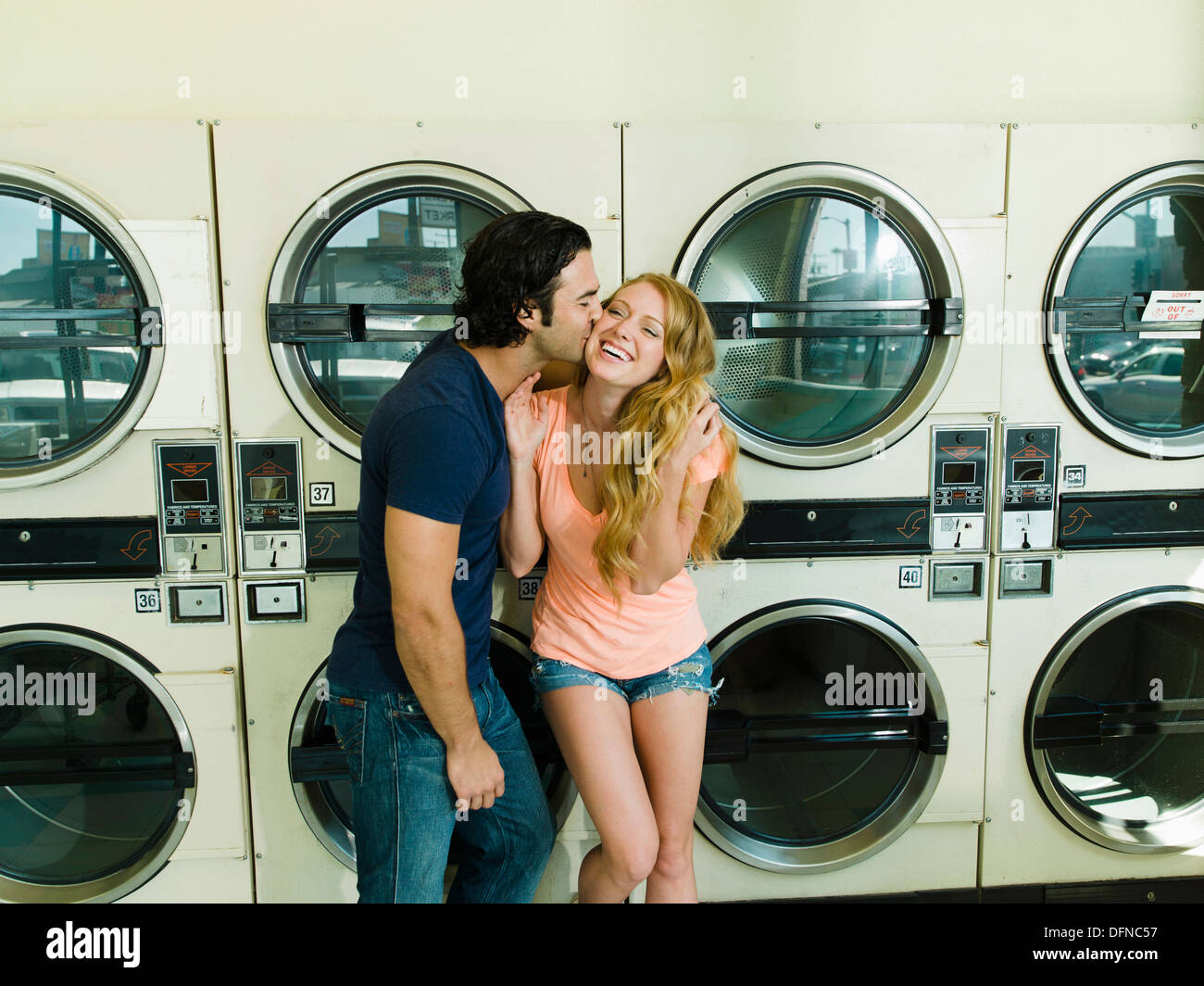 A young man kisses on the chick of a pretty woman in San Diego coin laundromat. Stock Photo