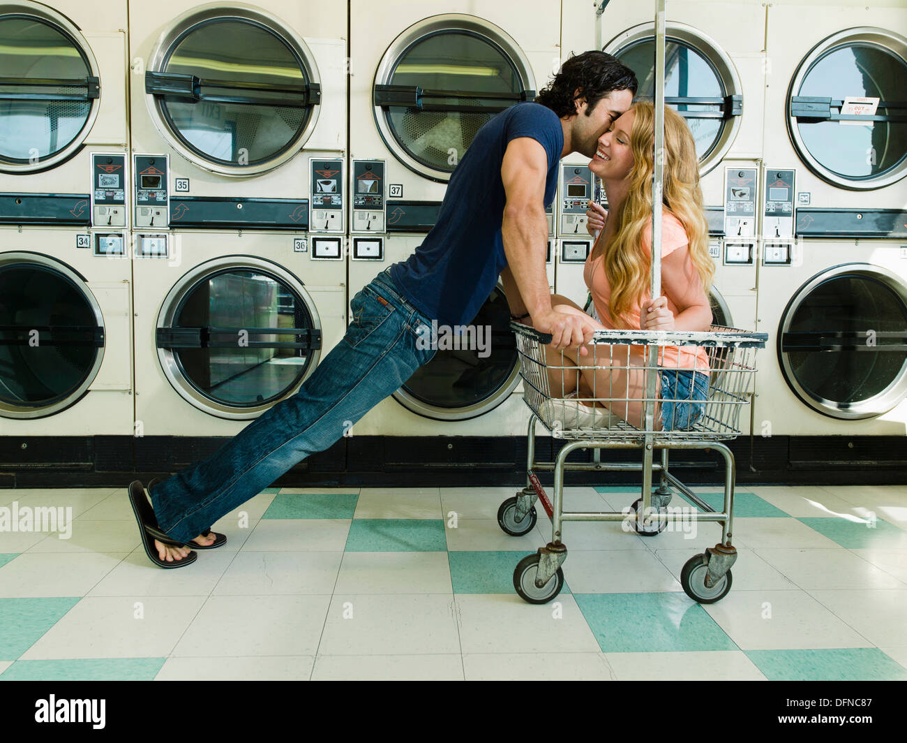 A young man leans over a pretty woman sits on a wheeled basket to kisses her chick in San Diego coin laundromat. - Stock Image