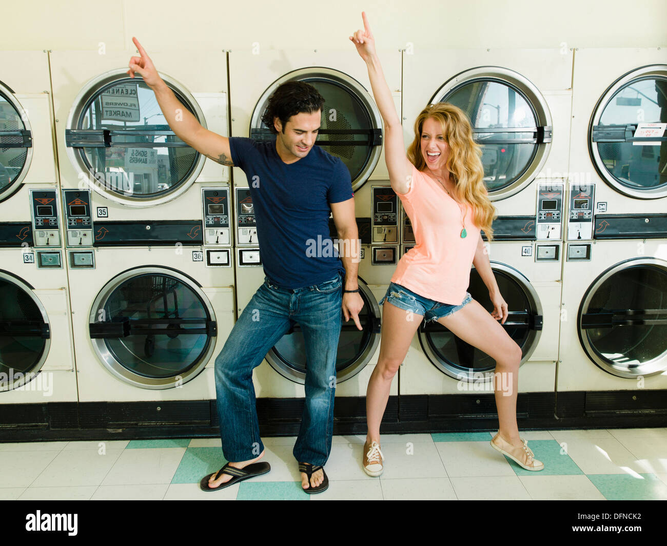 A beautiful lady dances with a smart young man in San Diego coin laundromat. - Stock Image
