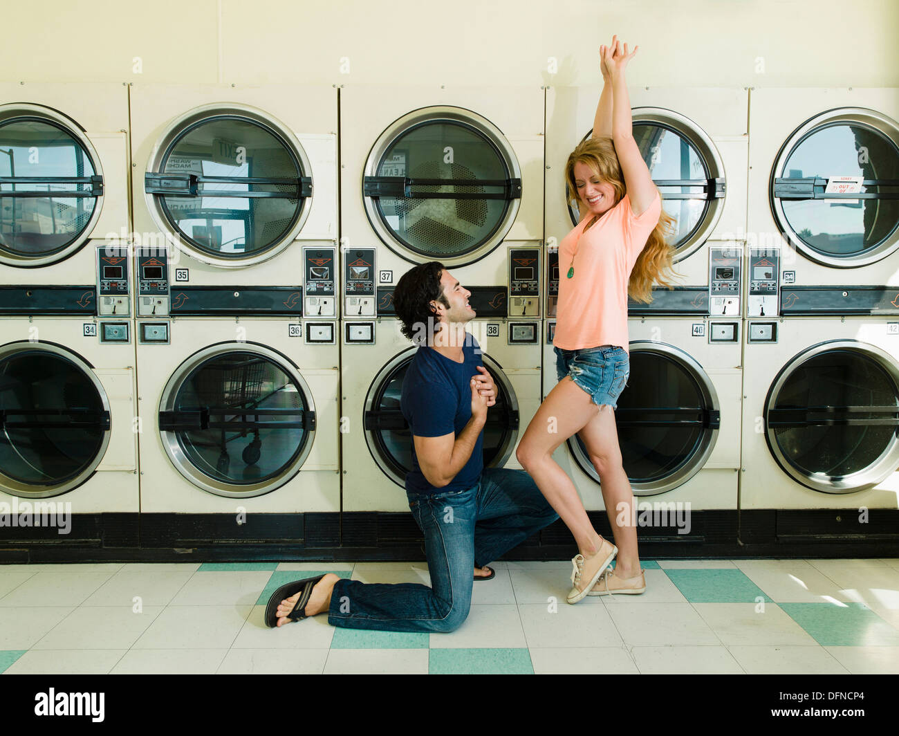 A smart young man kneels down before a beautiful woman in San Diego coin laundromat. - Stock Image
