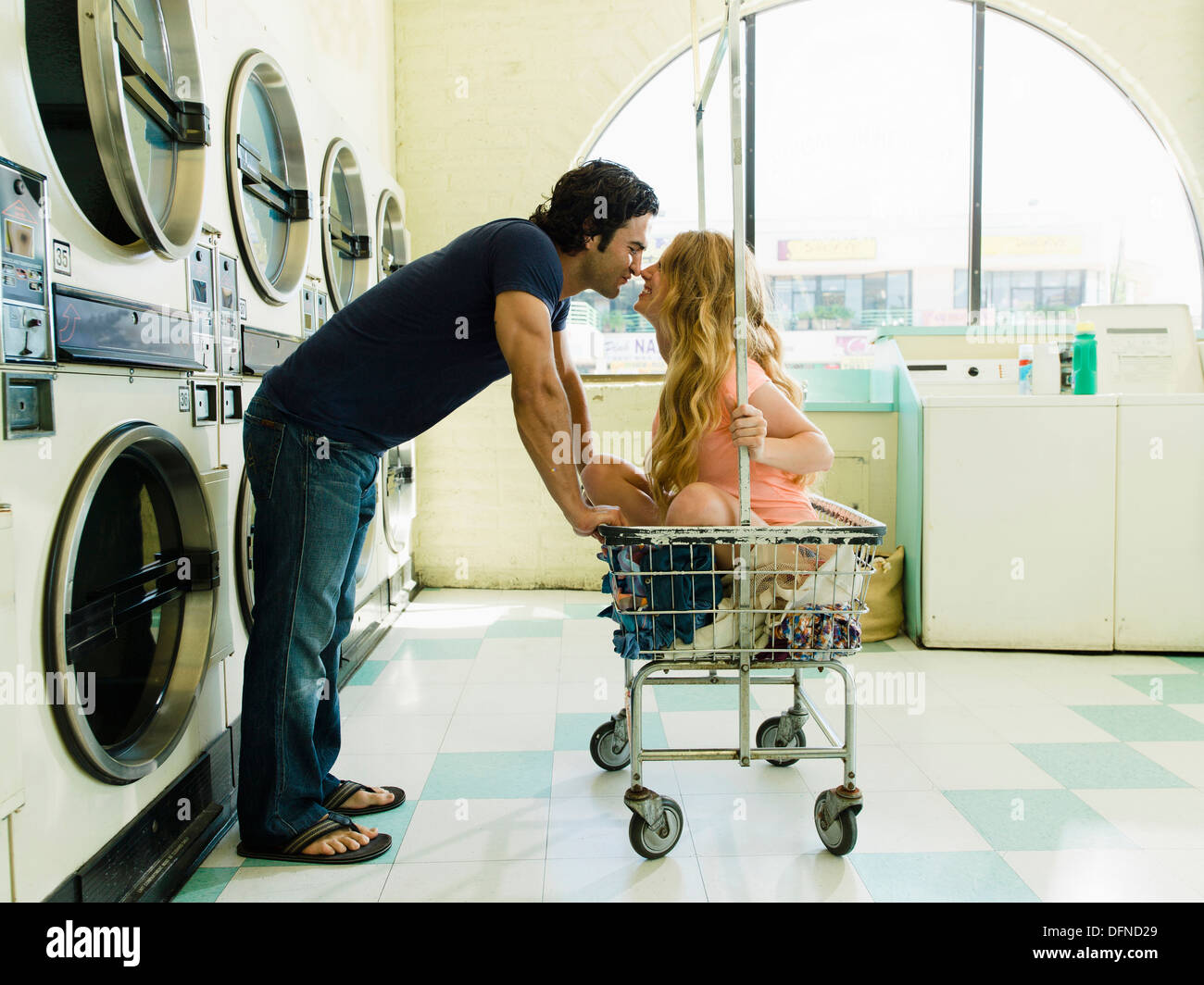 A young man leans over to feel the nose of a beautiful lady who sits on wheeled basket in San Diego coin laundromat. - Stock Image