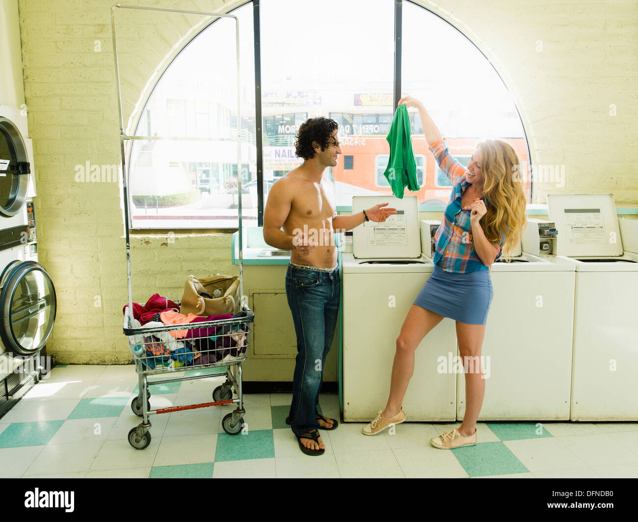 A pretty woman hangs a T-shirt before a bared body young man in San Diego coin laundromat. - Stock Image