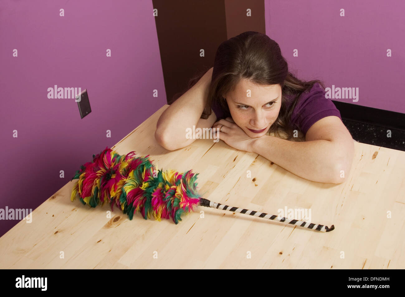 Young woman sitting next to a feather duster - Stock Image