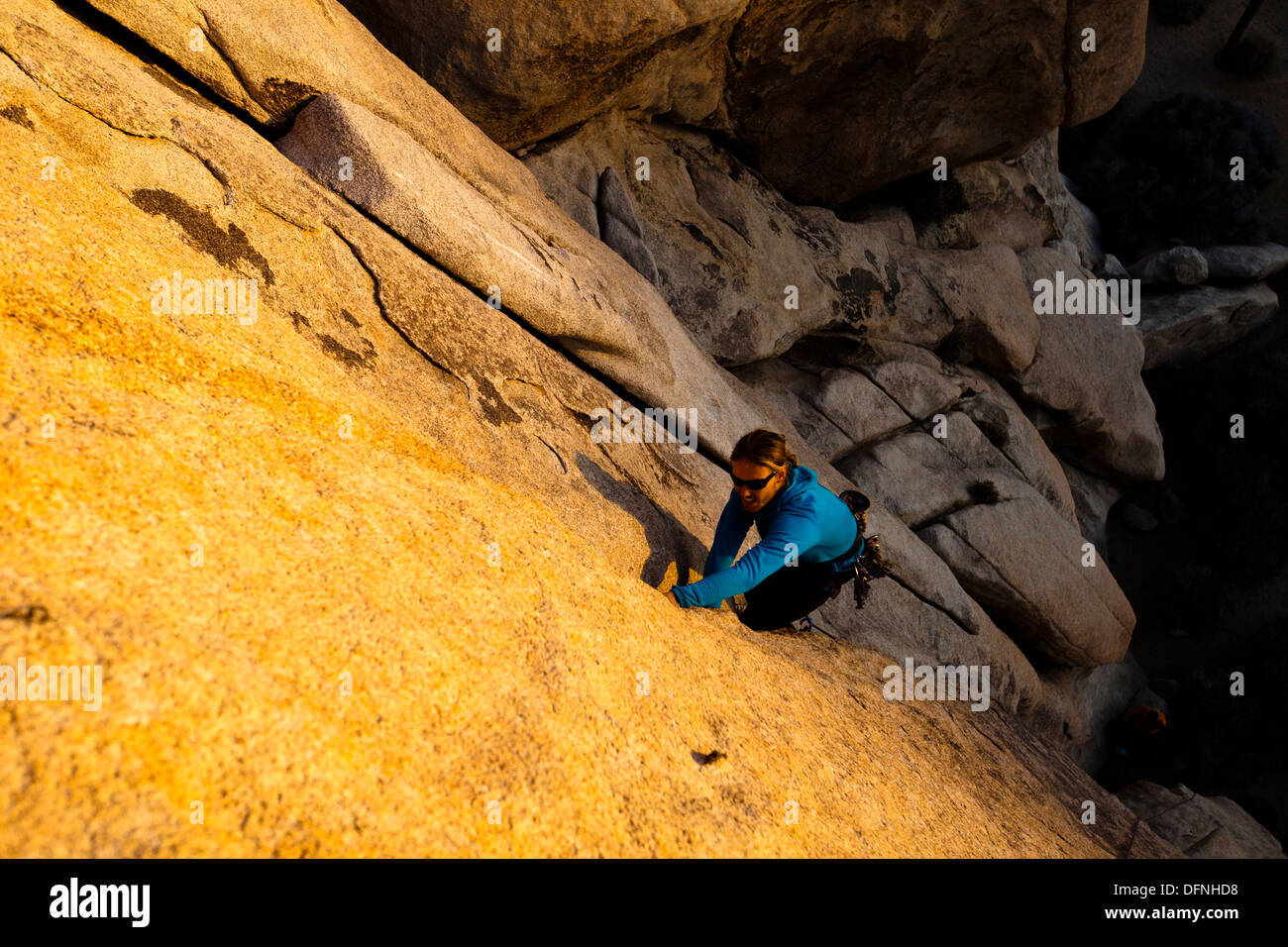 A male climber hand jams his way up The Flake (5.8+) in Joshua Tree National Park, California. - Stock Image